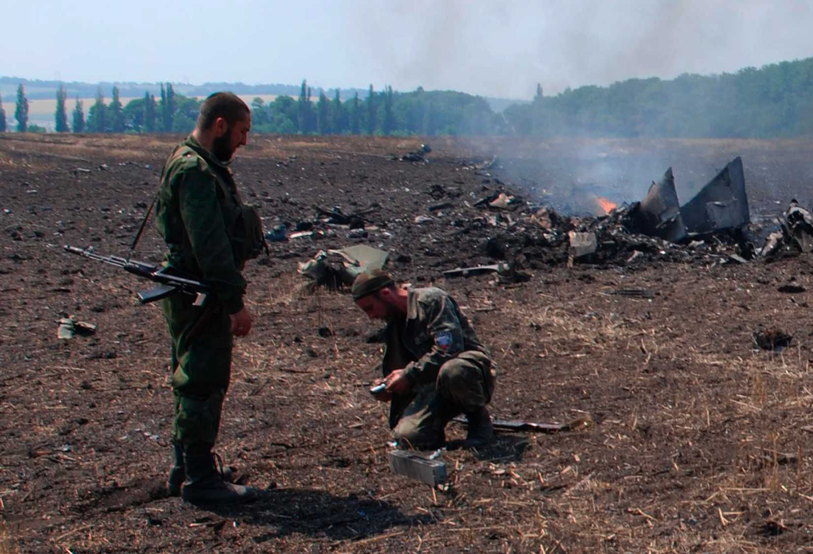 In this framegrab made from a video provided by press service of the rebel Donetsk People's Republic and icorpus.ru, pro-Russians collect parts of the burning debris of a Ukrainian military fighter jet, shot down at Savur Mogila, eastern Ukraine, Wednesday, July 23, 2014.