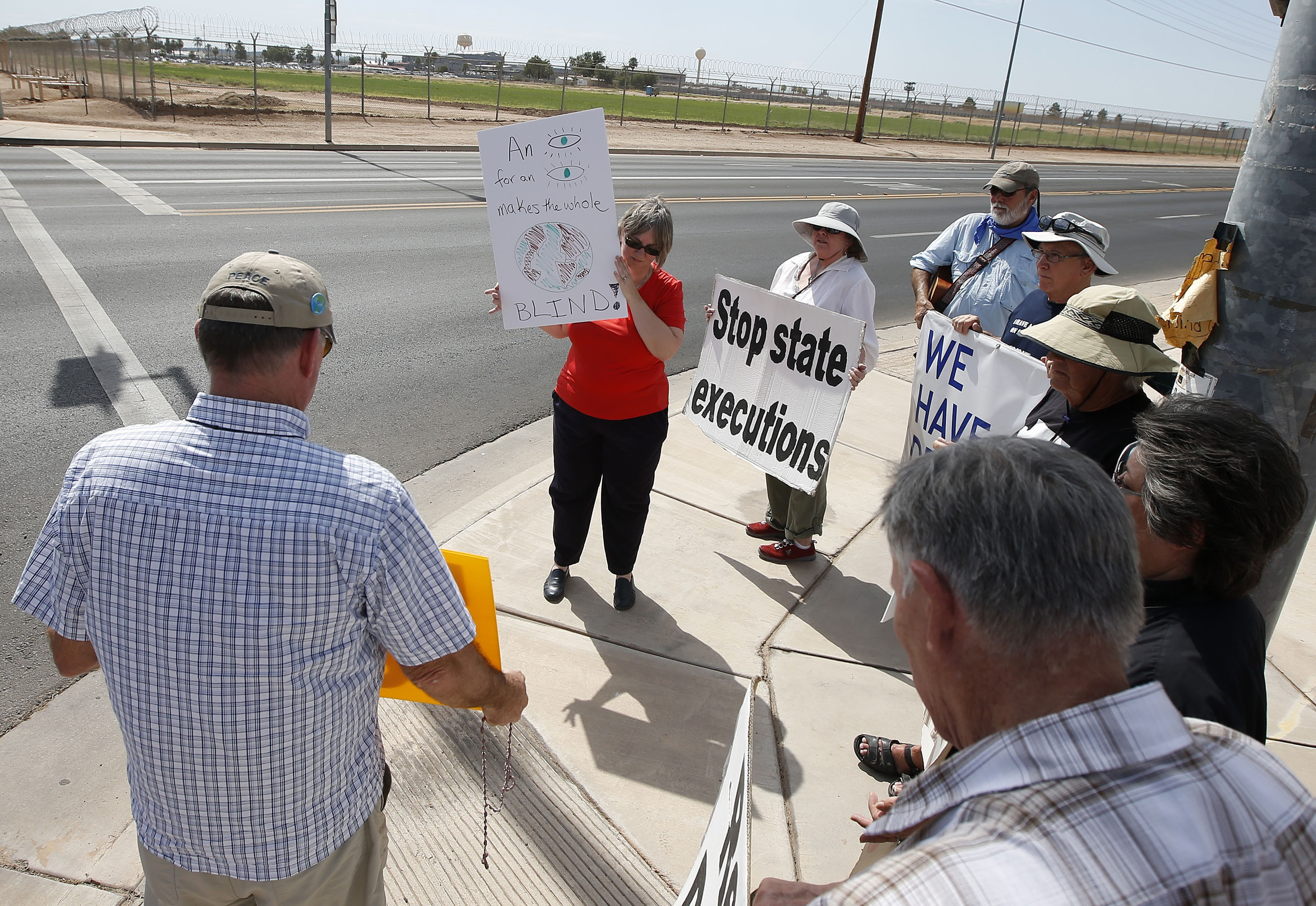 With the state prison in the background, about a dozen death-penalty opponents pray as they await the execution of Joseph Wood in Florence, Ariz., on July 23, 2014