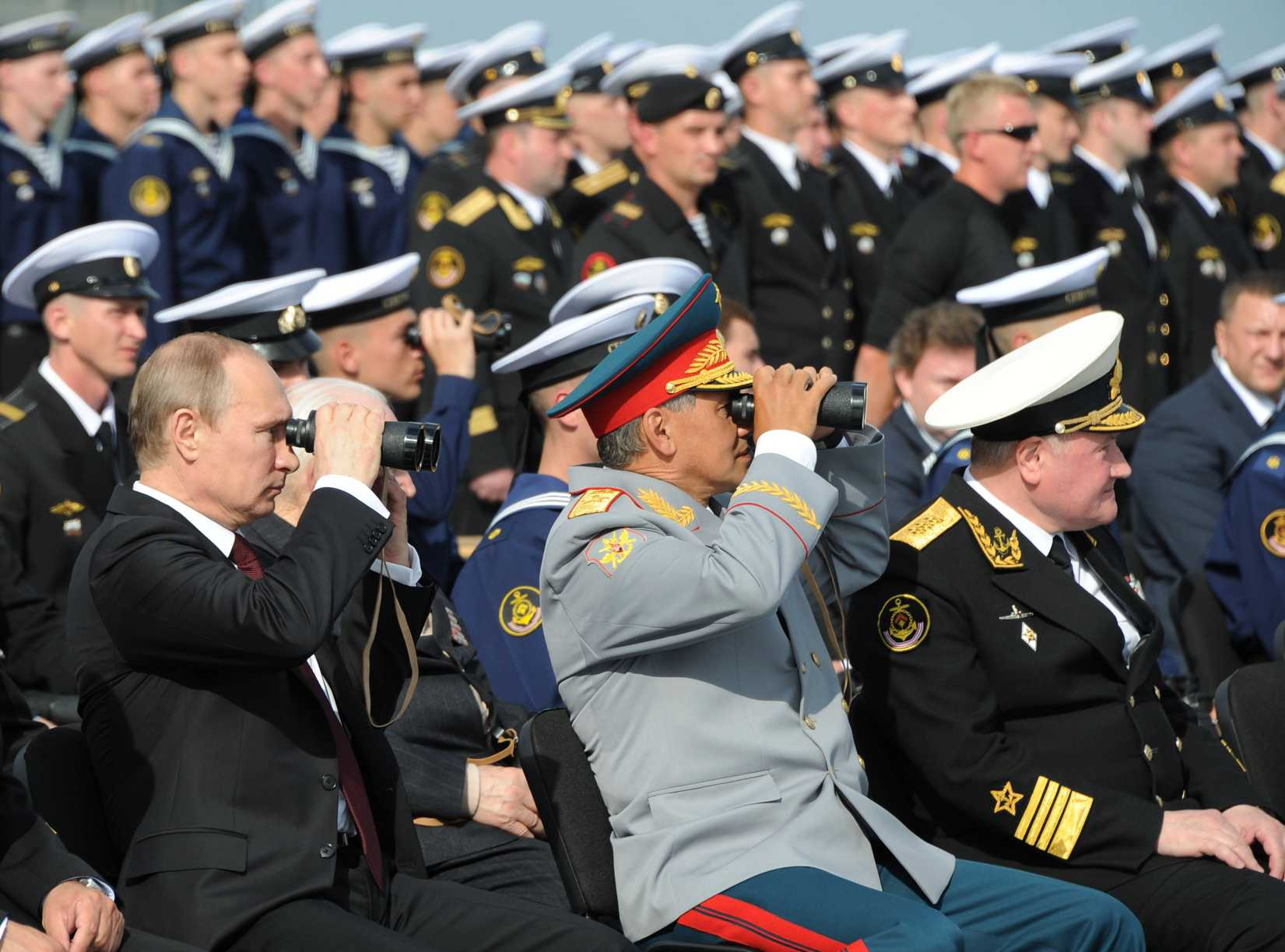 Russian President Vladimir Putin, left, and Russian Defense Minister Sergei Shoigu, center, use binoculars to watch a parade marking the country's Navy Day in Severomorsk, Russia, In this Sunday, on July 27, 2014