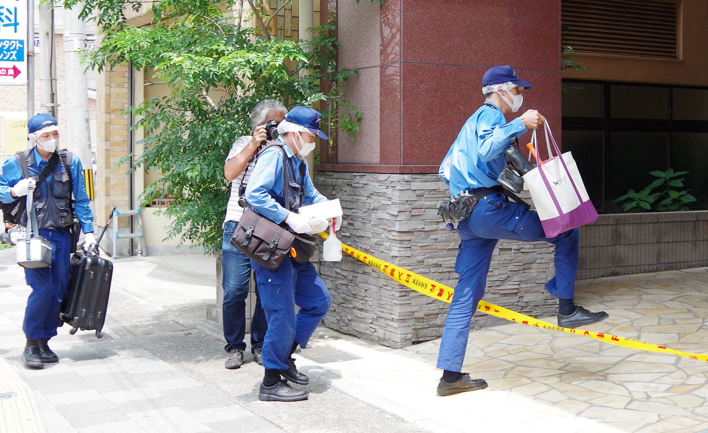 Japanese police officers enter an apartment building in Sasebo, in Nagasaki prefecture, Japan, on July 27, 2014, to investigate the site where Aiwa Matsuo, a 15-year-old high school girl, was murdered by her classmate