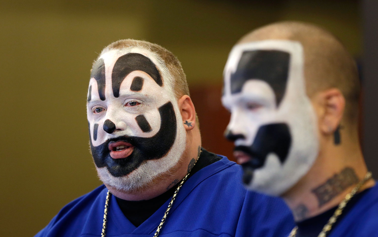 Joseph Bruce, aka Violent J, left, and Joseph Utsler, aka Shaggy 2 Dope, members of the Insane Clown Posse, address the media in Detroit, Jan. 8, 2014. The U.S. Justice Department is asking a judge to dismiss a lawsuit by Insane Clown Posse, which objects to a report that describes its fans as a dangerous gang.