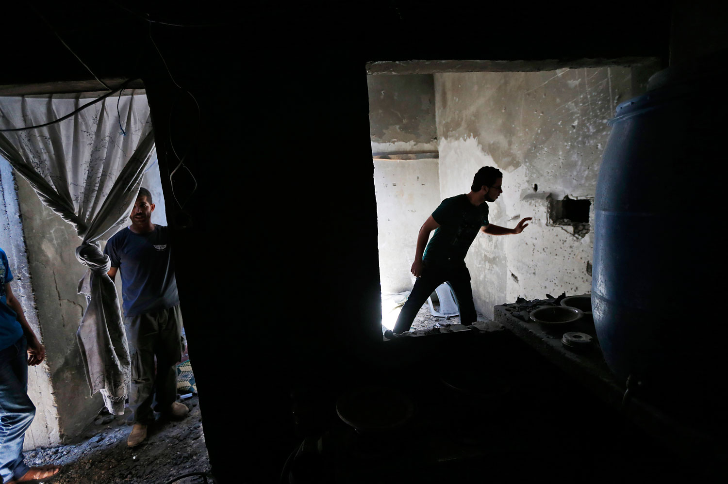 A Palestinian inspects a hole made by an Israeli strike at the damaged Inteiz family house in the Shajaiyeh neighborhood of Gaza City, northern Gaza Strip, July 18, 2014.