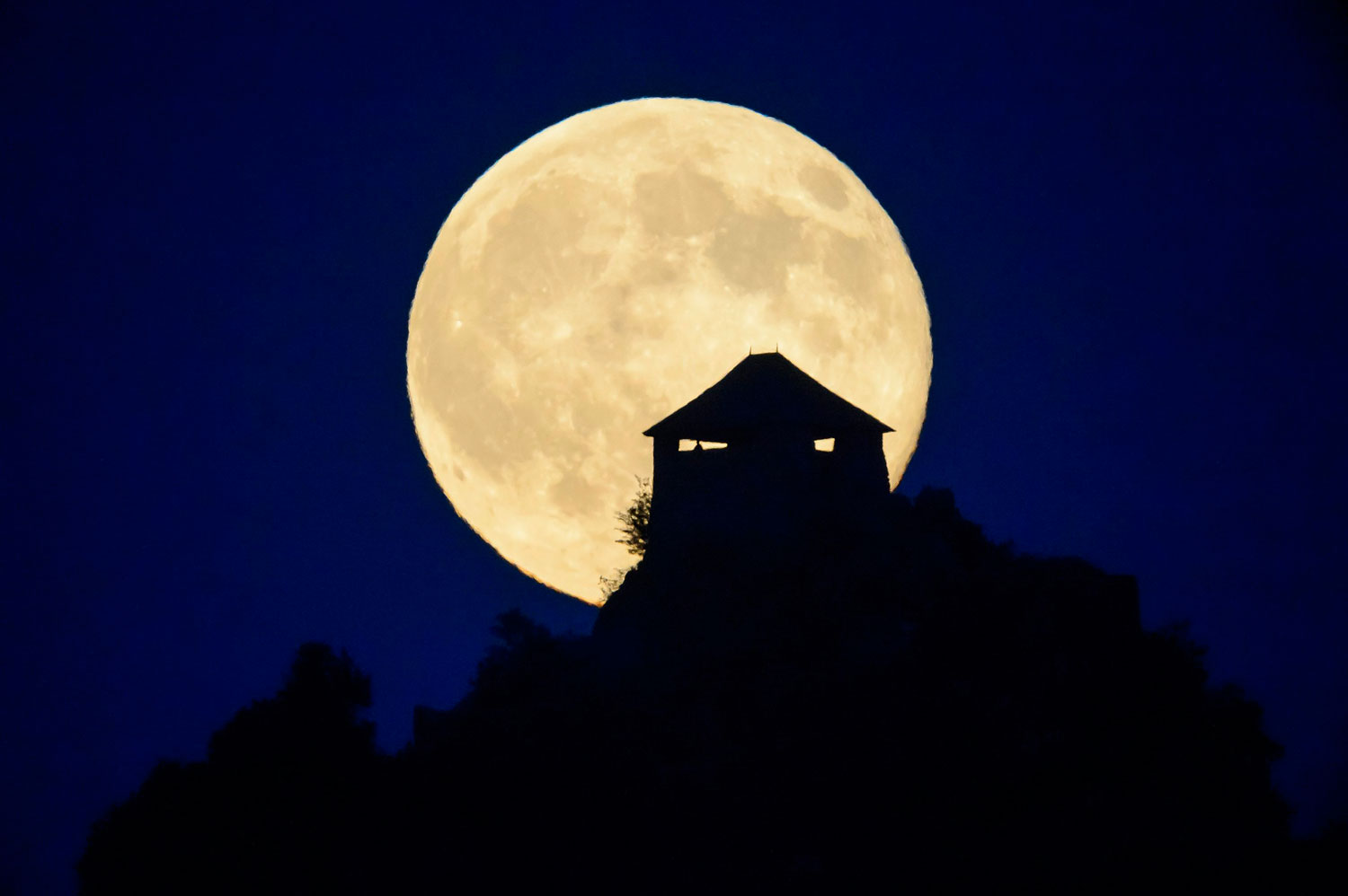 The full moon rises above the castle of Somoskoujfalu, 123 kms northeast of Budapest, Hungary, late Saturday, July 12, 2014.