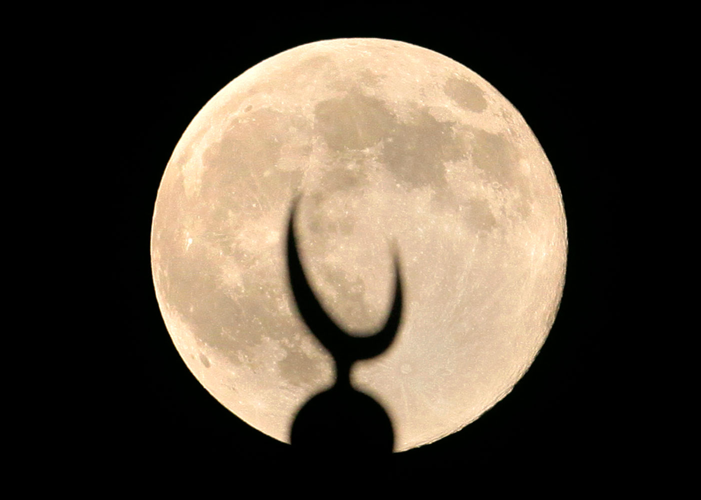 A perigee moon, also known as a supermoon, rises over a crescent of a minaret of grand Faisal mosque in Islamabad, Pakistan, July 12, 2014.