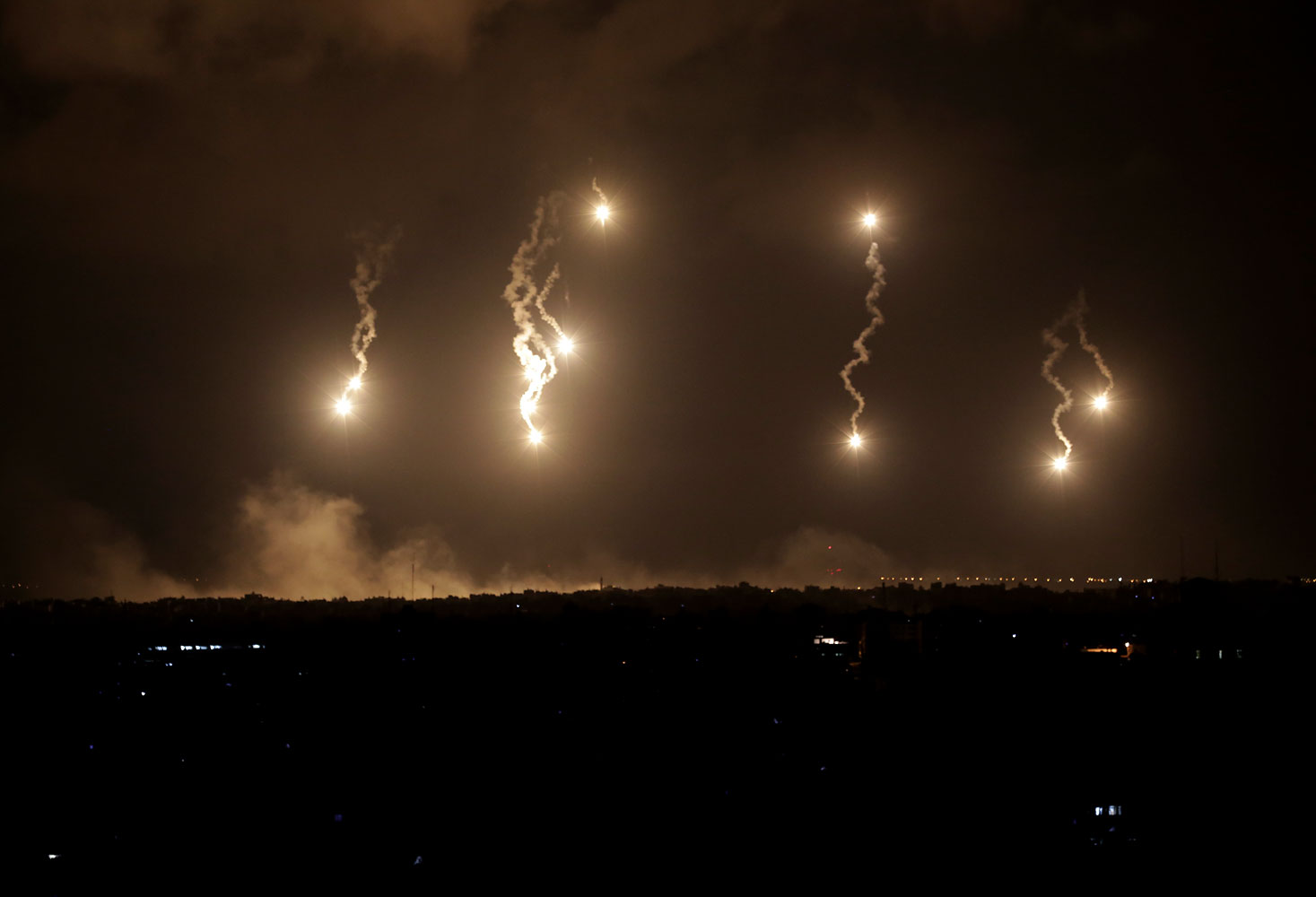 Israeli forces' flares light up the night sky in the northern Gaza Strip, early Saturday, July 19, 2014.