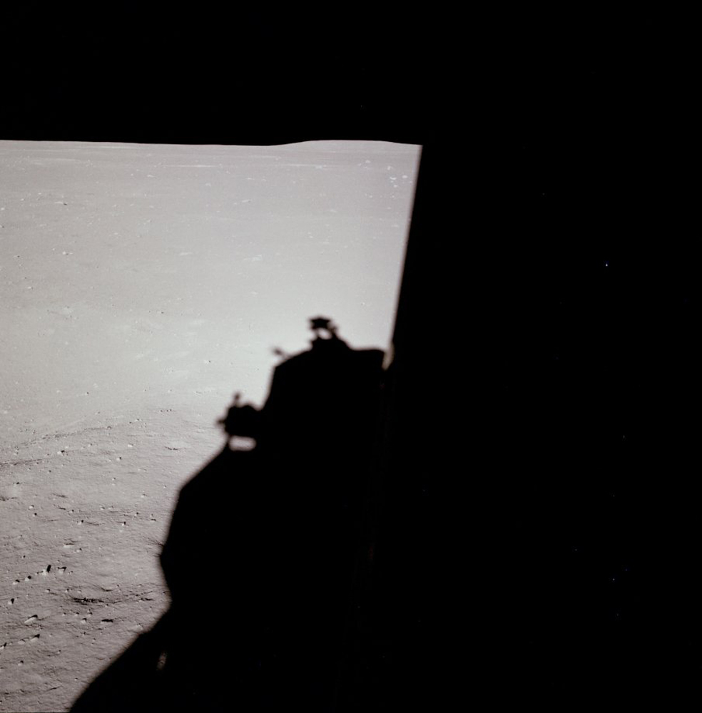 Down-Sun (west) view of the lunar surface just after landing with the Lunar Module shadow, lunar horizon and a partial view of a shallow crater to the left of the Lunar Module shadow.