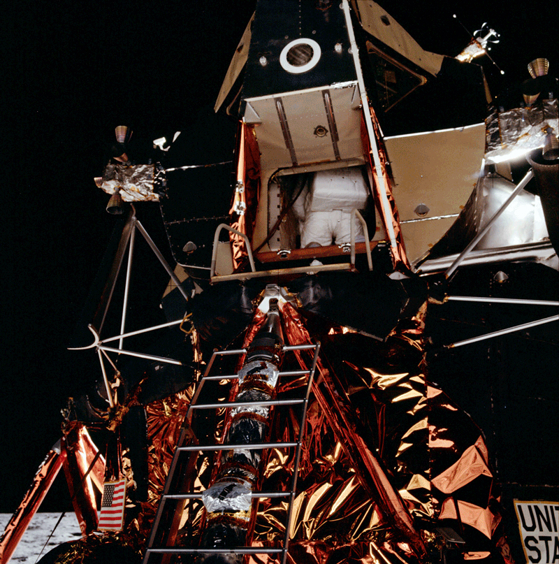 The first photo taken of Buzz coming out through the hatch of the Lunar Module . The US flag that Neil and Buzz will deploy later, is stowed in a long, thin canister attached to the underside of the lefthand rail of the ladder.