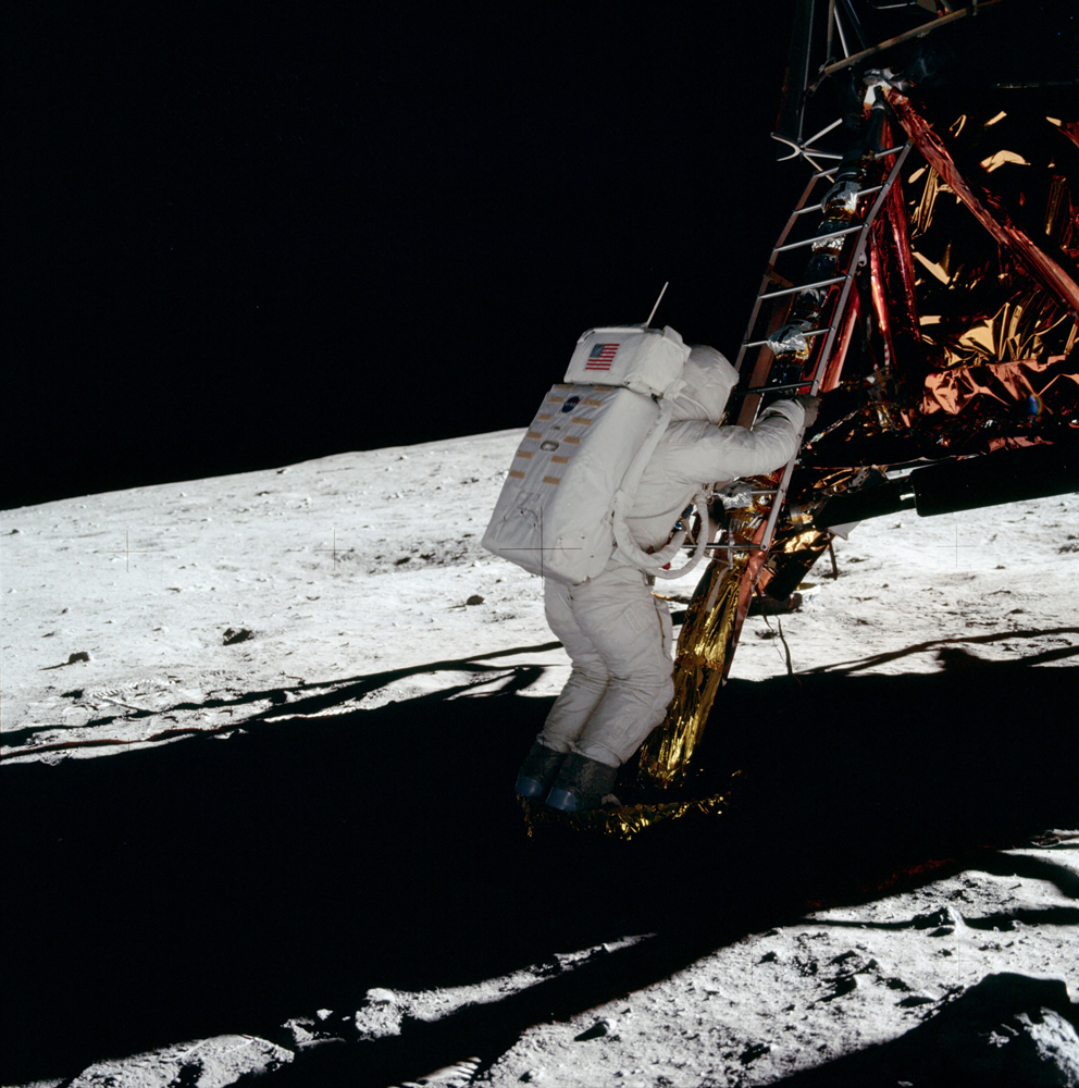 Buzz has both feet on the footpad. His communications antenna is visible.
