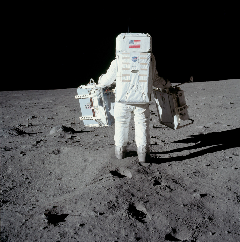 This photograph is the first in a sequence of pictures Neil took of Buzz carrying part of the mission's experiment package out to the deployment site a short way south of the spacecraft. The piece of equipment in his right hand is a laser reflector, used to measure the Earth-moon distance precisely. A seismometer package is in Buzz's left hand.