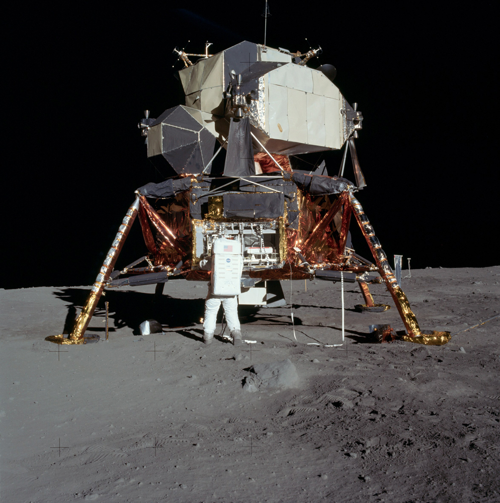 Buzz is preparing to remove the seismometer from the lefthand compartment in the equipment bay. He used a pulley-mounted tape to raise the door which can be seen above the right side of the bay. The tape is visible to his right, draped over a Lunar Module strut.