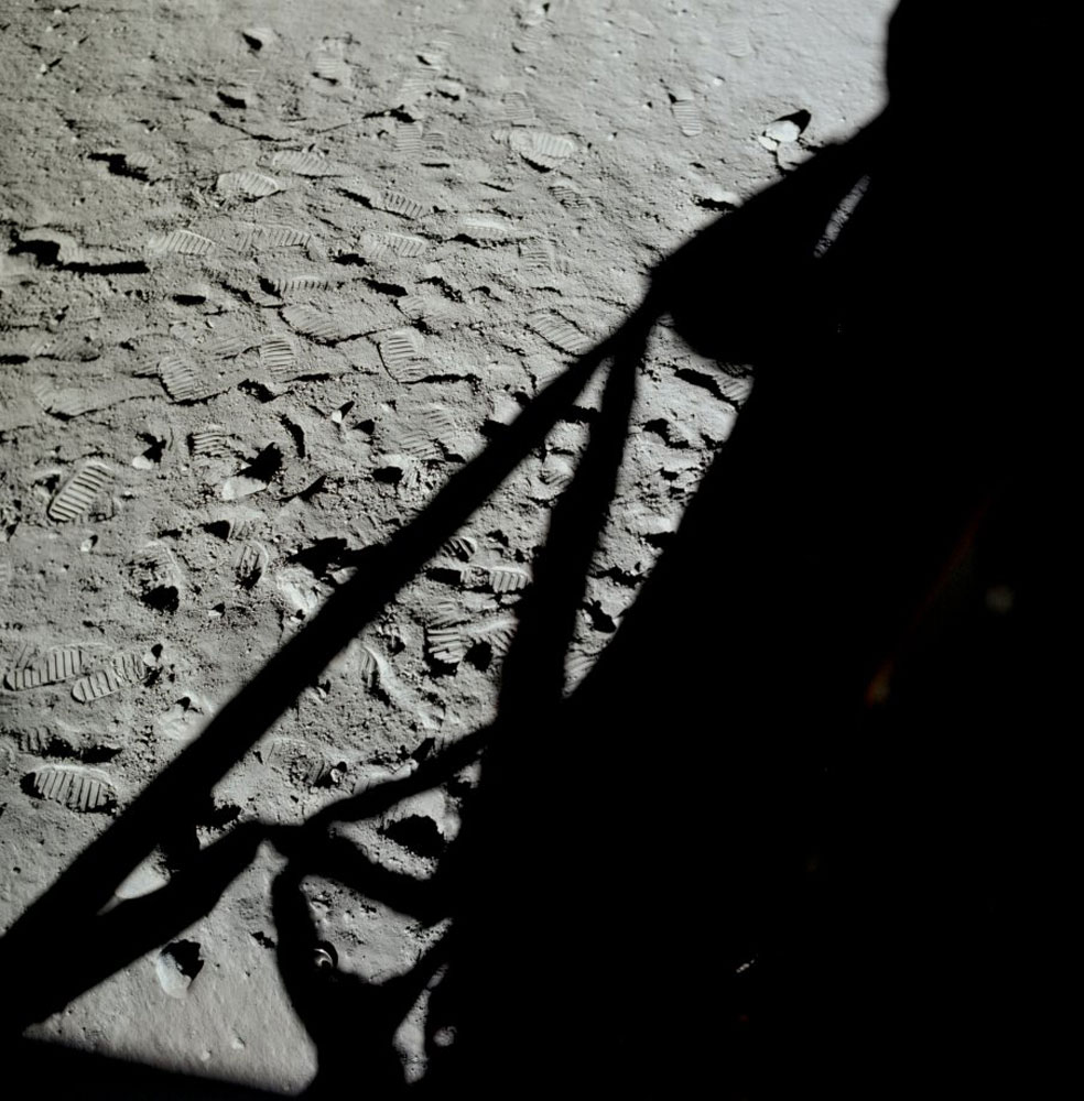 The black shadow of the Lunar Module is silhouetted against the Moon's surface in this photograph taken out Neil's window after the crew had returned to the LM. Impressions in the lunar soil made by the lunar boots of the two astronauts are clearly visible.