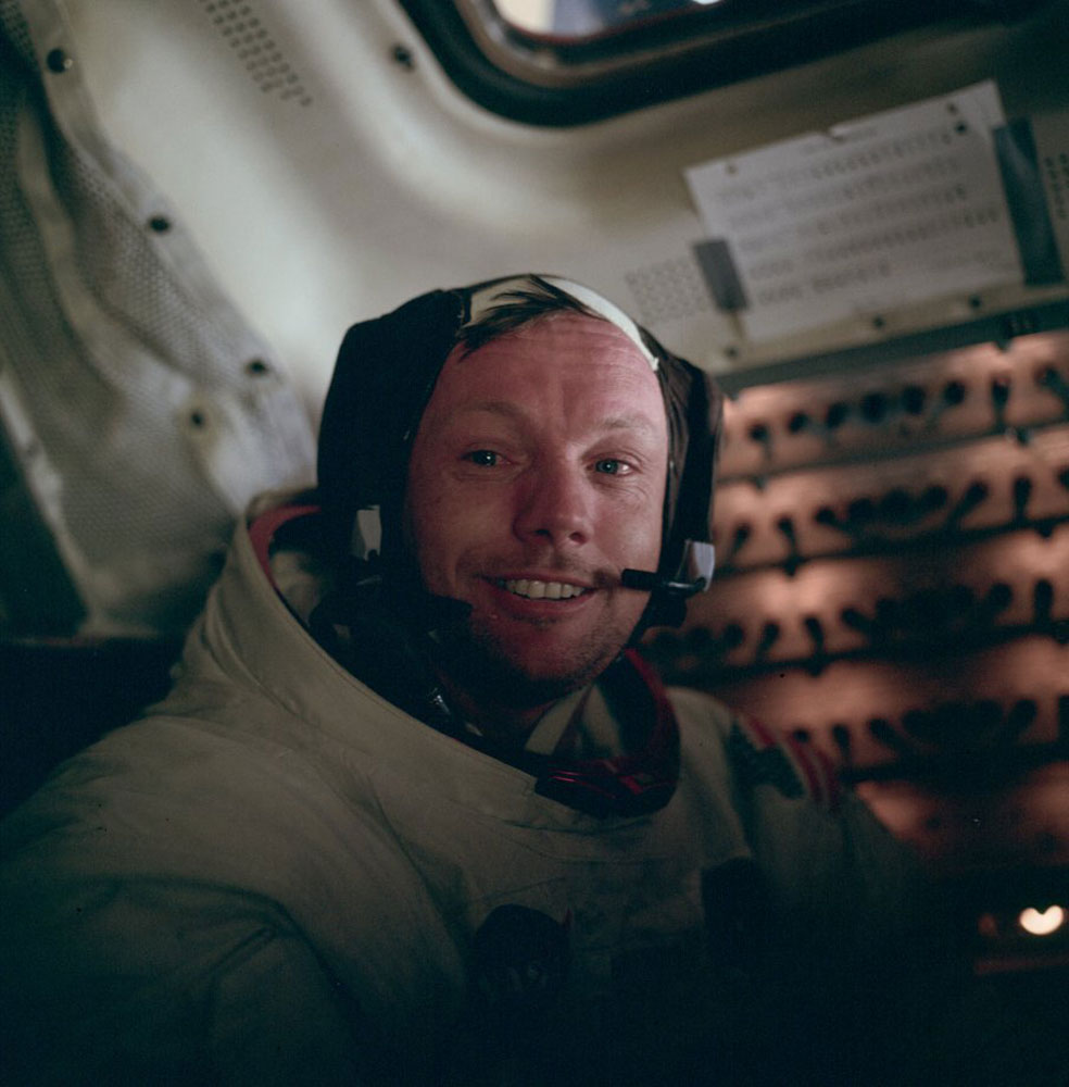 Buzz took this picture of Neil in the cabin after the completion of the moonwalk. Neil has his helmet off but has not yet removed his  Snoopy  cap. The circuit breaker panels are illuminated, and a small floodlight is on at the lower right.