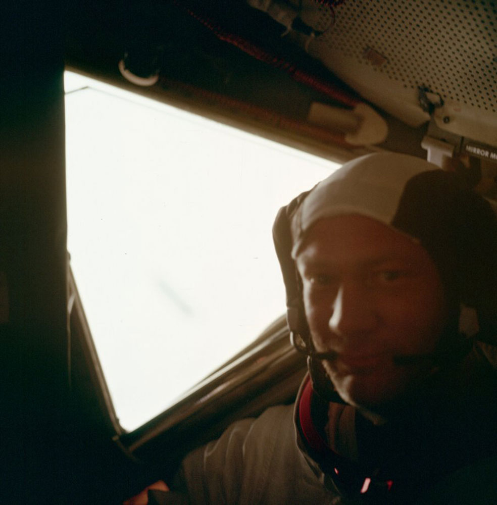 Buzz has handed the camera back to Neil again who attempts to make a portrait of Buzz in the cabin. The extremely bright light coming through the window is being reflected off of the lunar surface.
