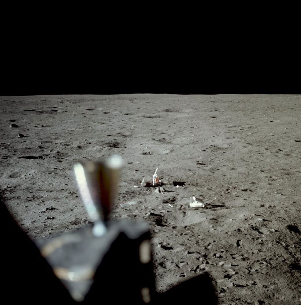 Neil documents the surface experiments south of the Lunar Module. Two components of the equipment package they left behind are seen:  the seismograph (left) and the laser reflector (right).