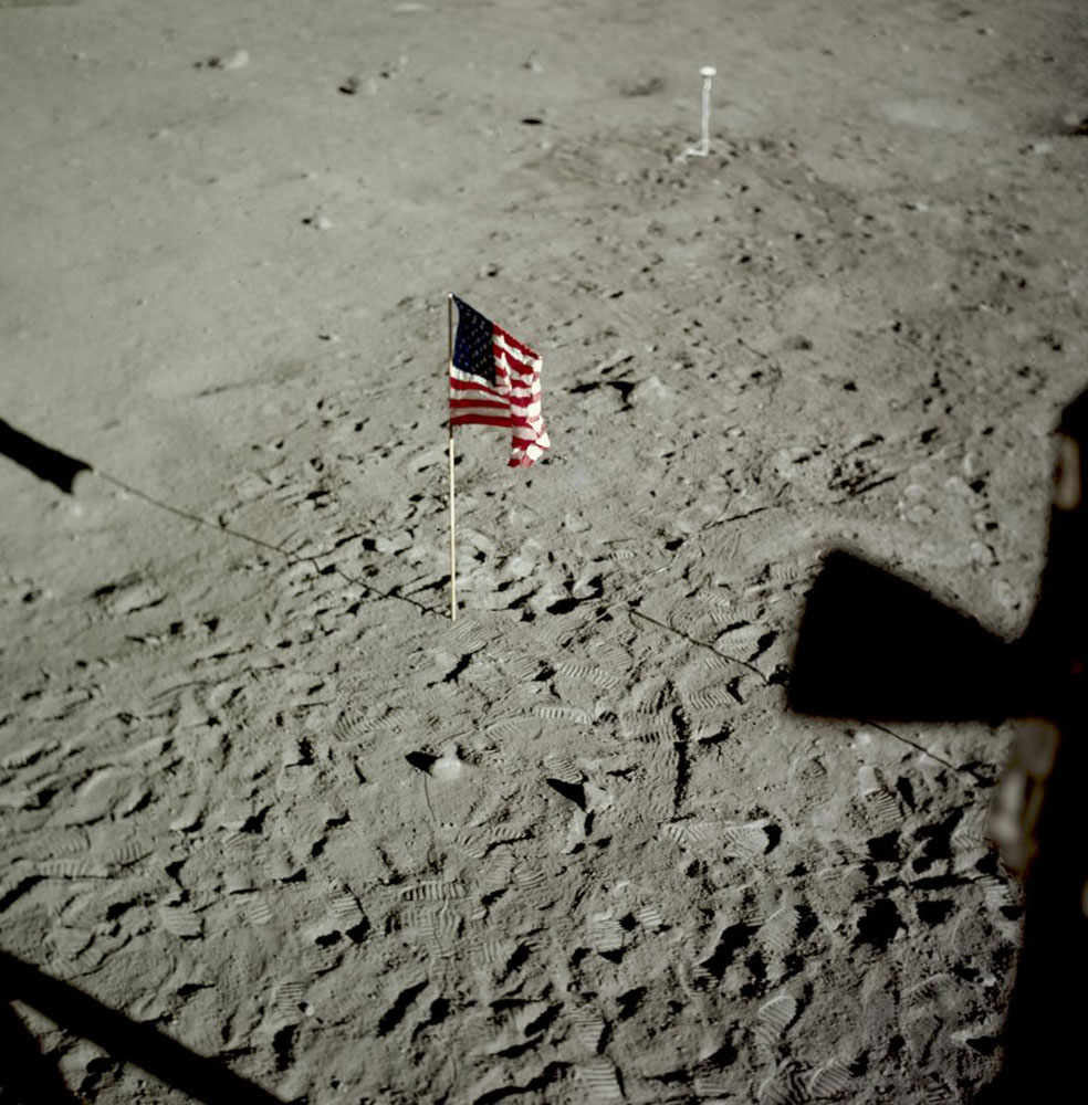 A view of the U.S. flag, deployed on the surface of the Moon and the deployed black and white lunar surface television camera which televised the lunar surface extravehicular activity in the background.