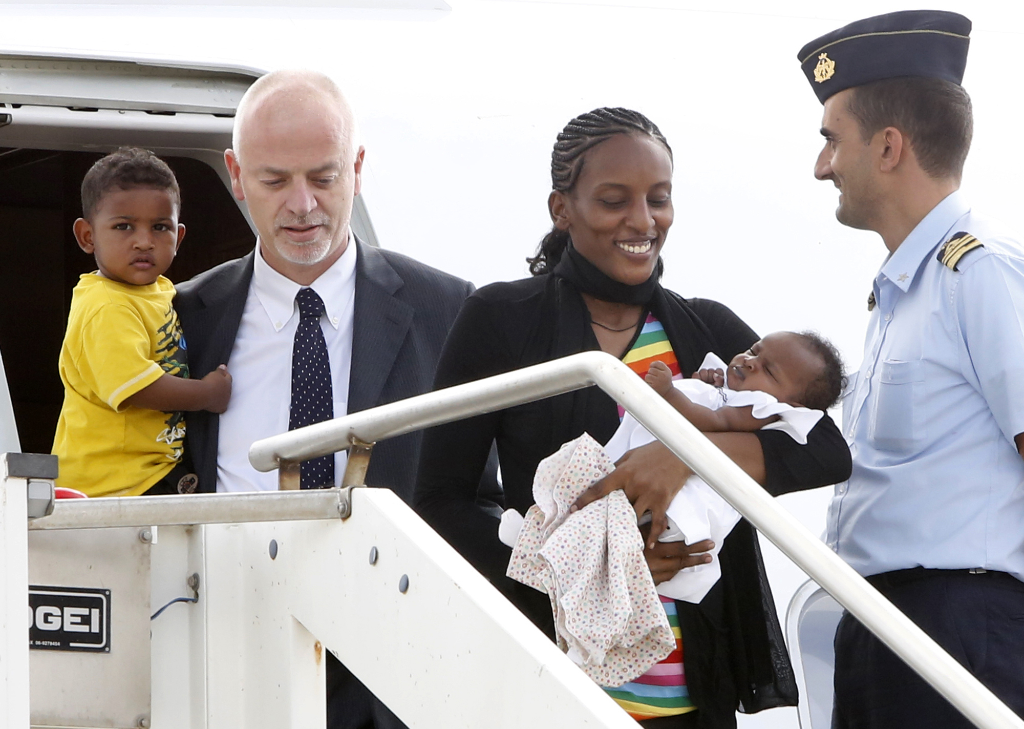 Mariam Ibrahim, from Sudan, disembarks with her children Maya, in her arms, and Martin, accompanied by Italian deputy Foreign Minister Lapo Pistelli, after landing from Khartoum, at Ciampino's military airport, on the outskirts of Rome, Thursday, July 24.