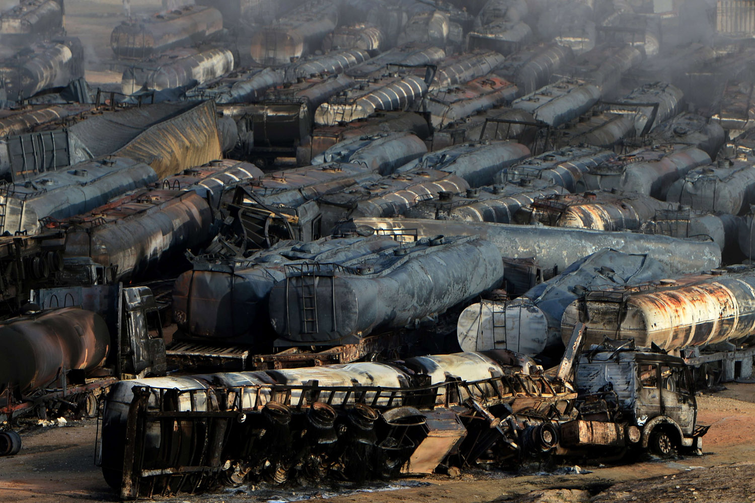 Jul. 5, 2014. Burned-out fuel trucks are seen following an overnight attack by Taliban militants in Chawk-e-Arghandi on outskirts of the Afghan capital Kabul.