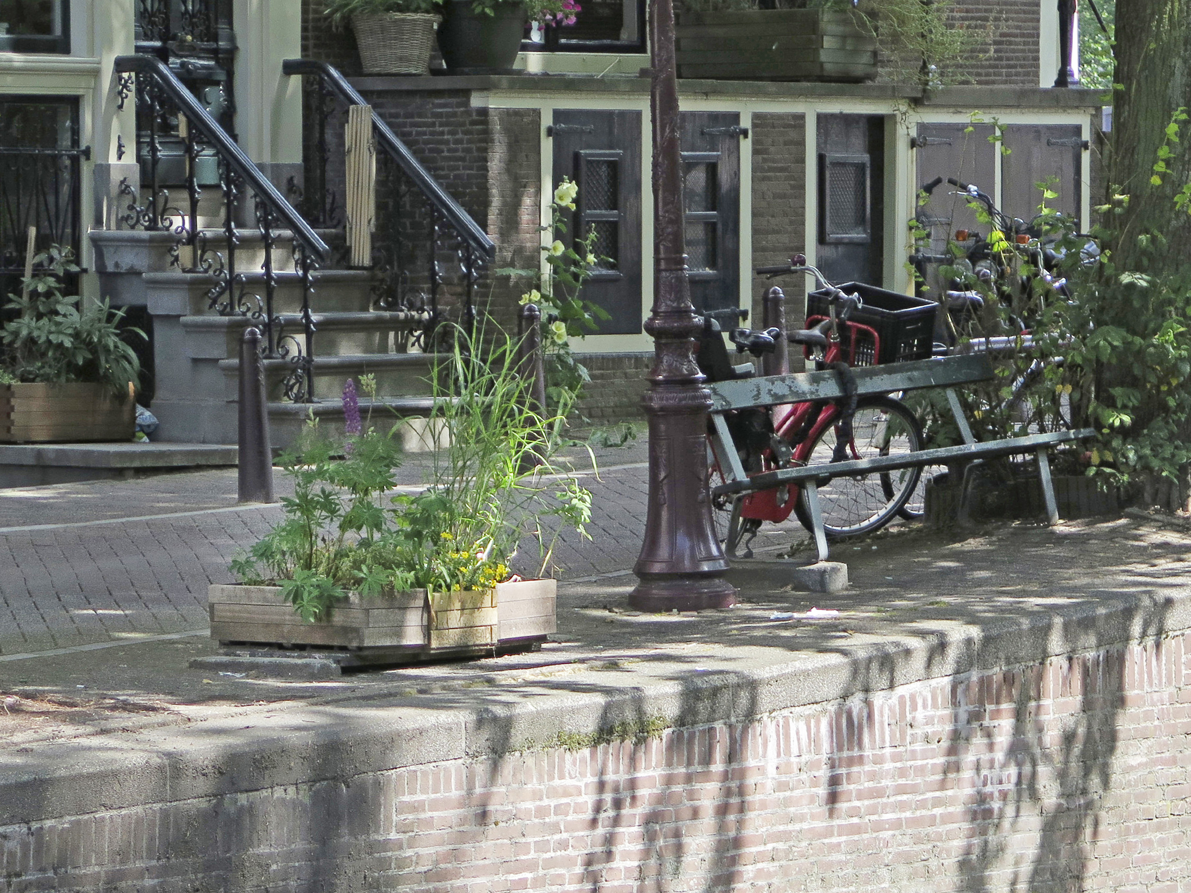 A large plant pot, at left, sits in the spot where a bench similar to the one at right, once sat, in Amsterdam on  July 1, 2014.
