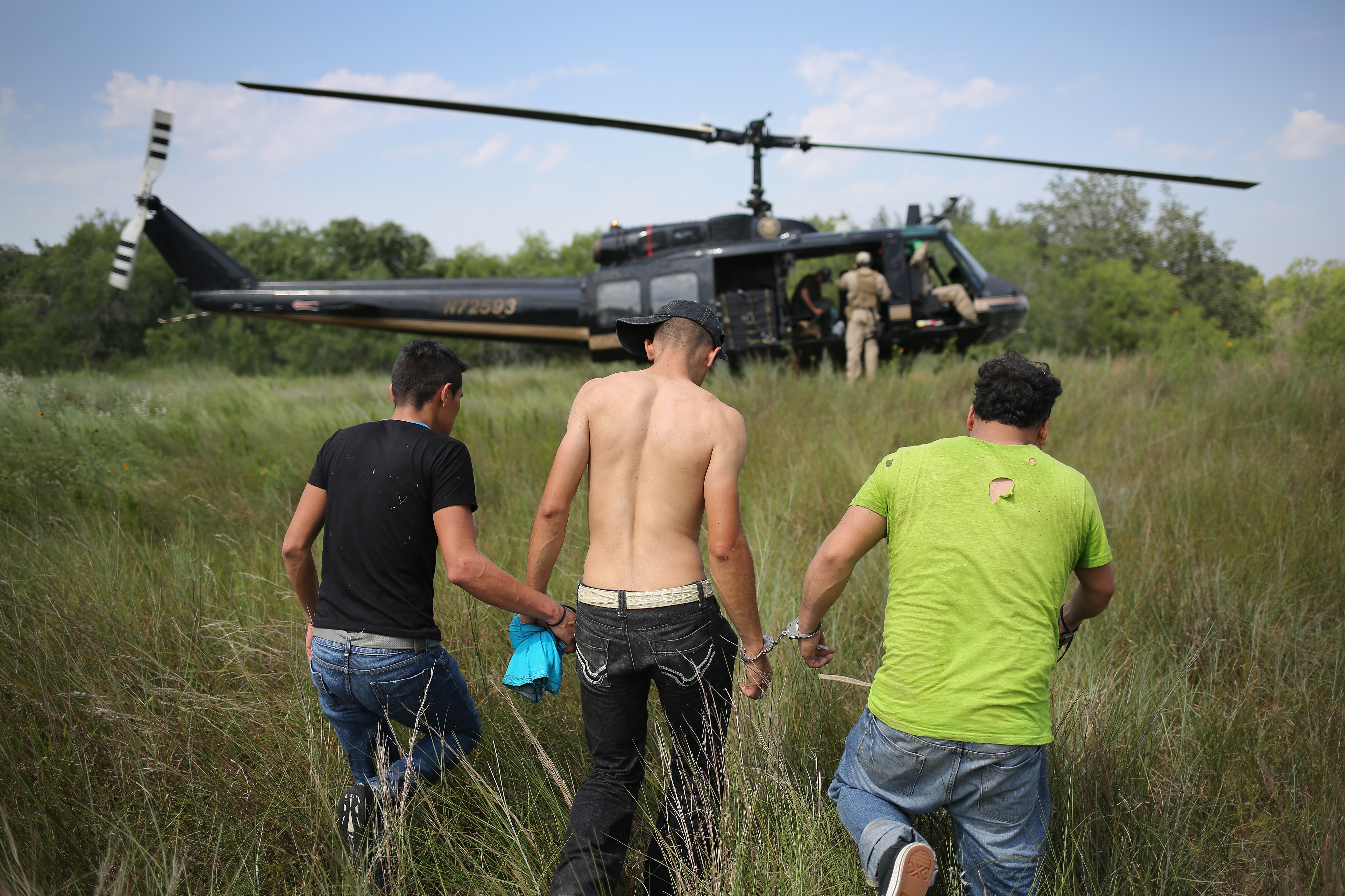 Undocumented immigrants await transport to a U.S. Customs and Border Protection processing center after being detained on July 22, 2014 near Falfurrias, Texas.