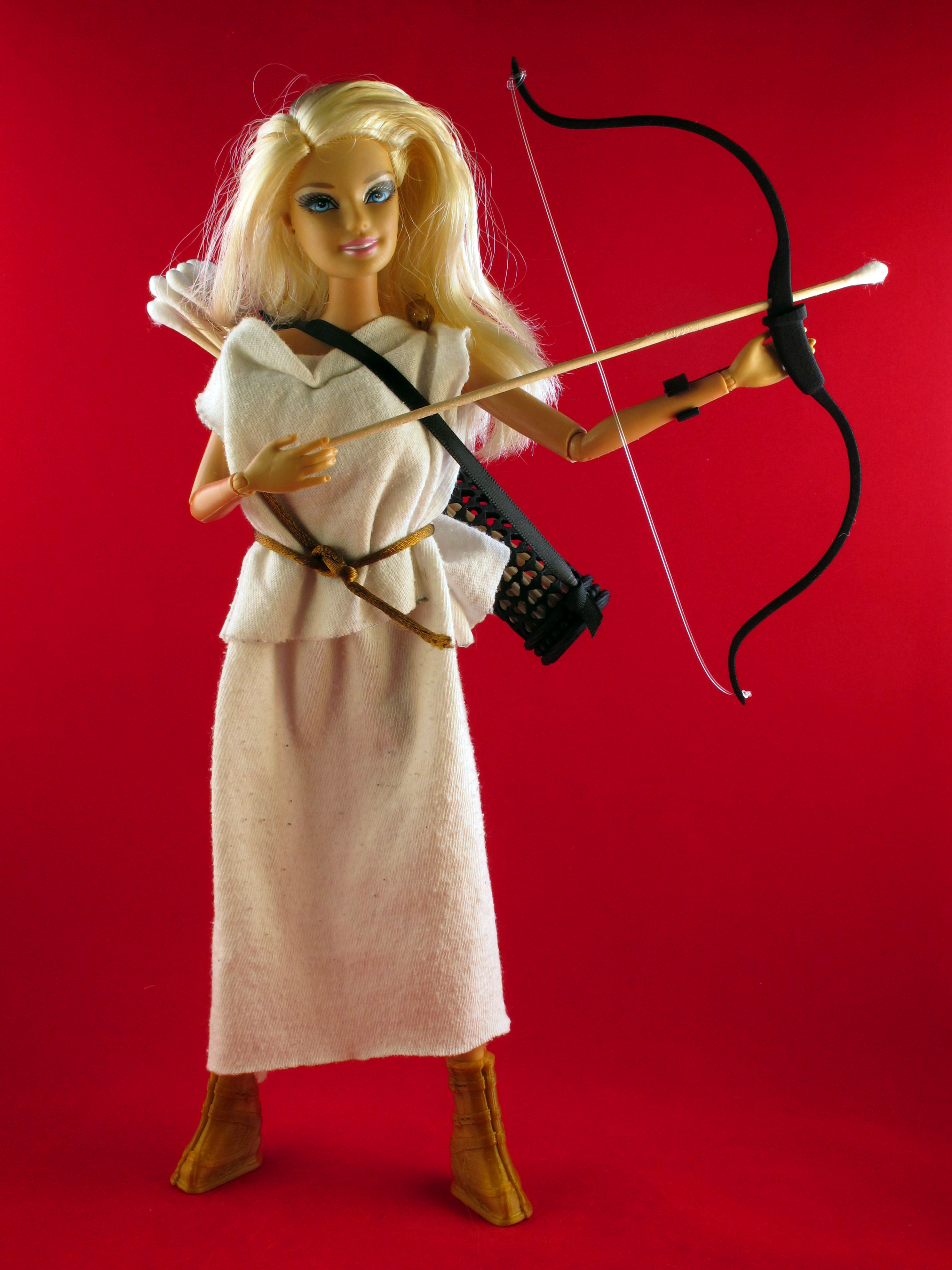 Barbie holds a bow and arrow in her medieval robe.