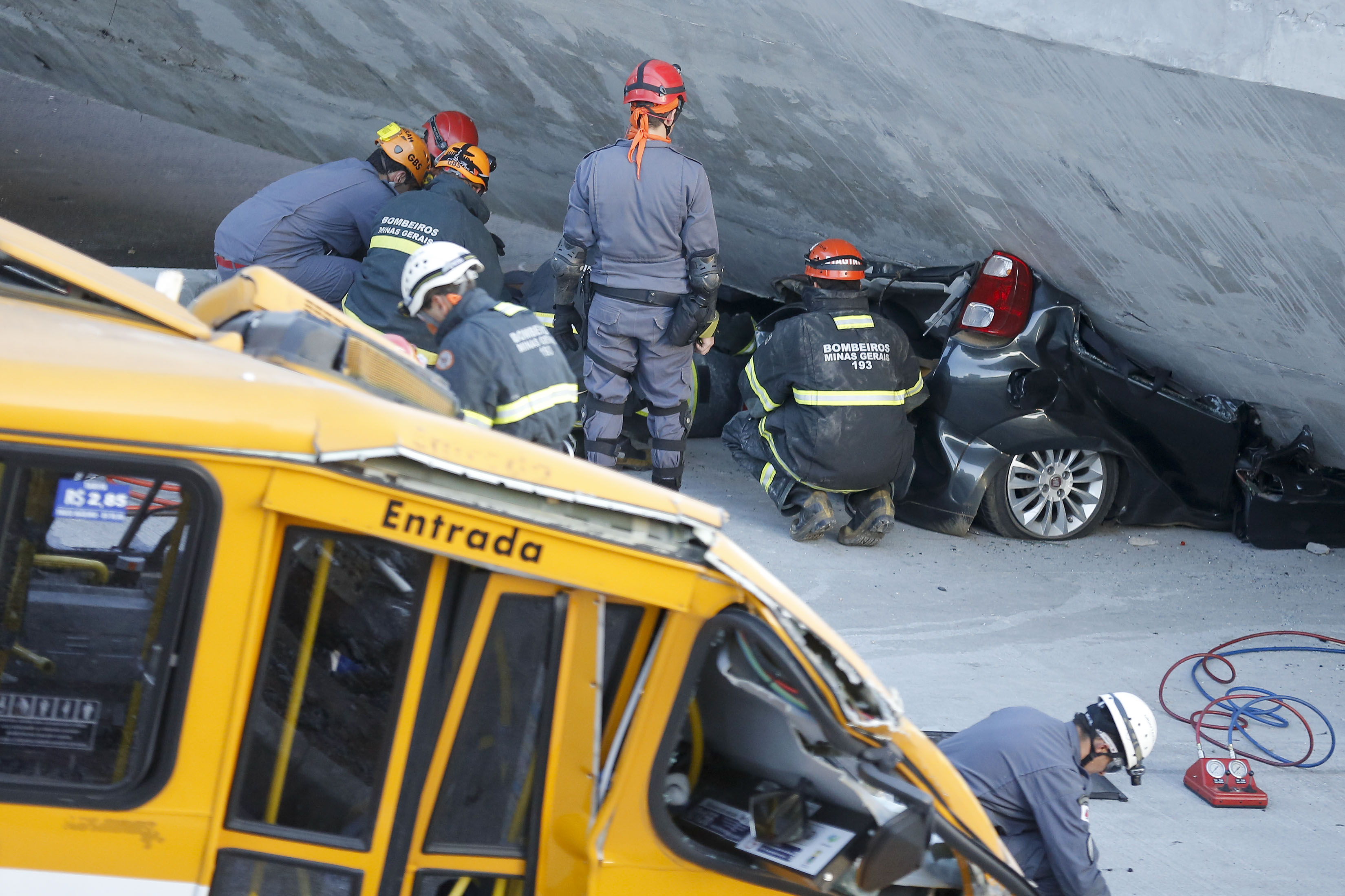 Fire department personnel work to retrieve a car from underneath a collapsed bridge in Belo Horizonte, Brazil, Thursday, July 3, 2014.