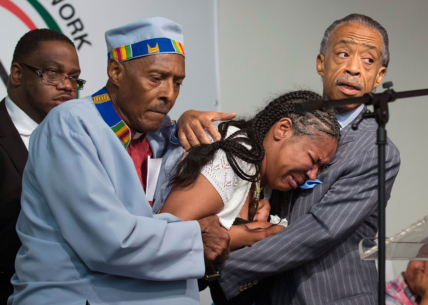 Rev. Herbert Daughtry and Rev. Al Sharpton hold Esaw Garner, wife of Eric Garner, during a rally at the National Action Network headquarters for Eric Garner, July 19, 2014, in New York City.