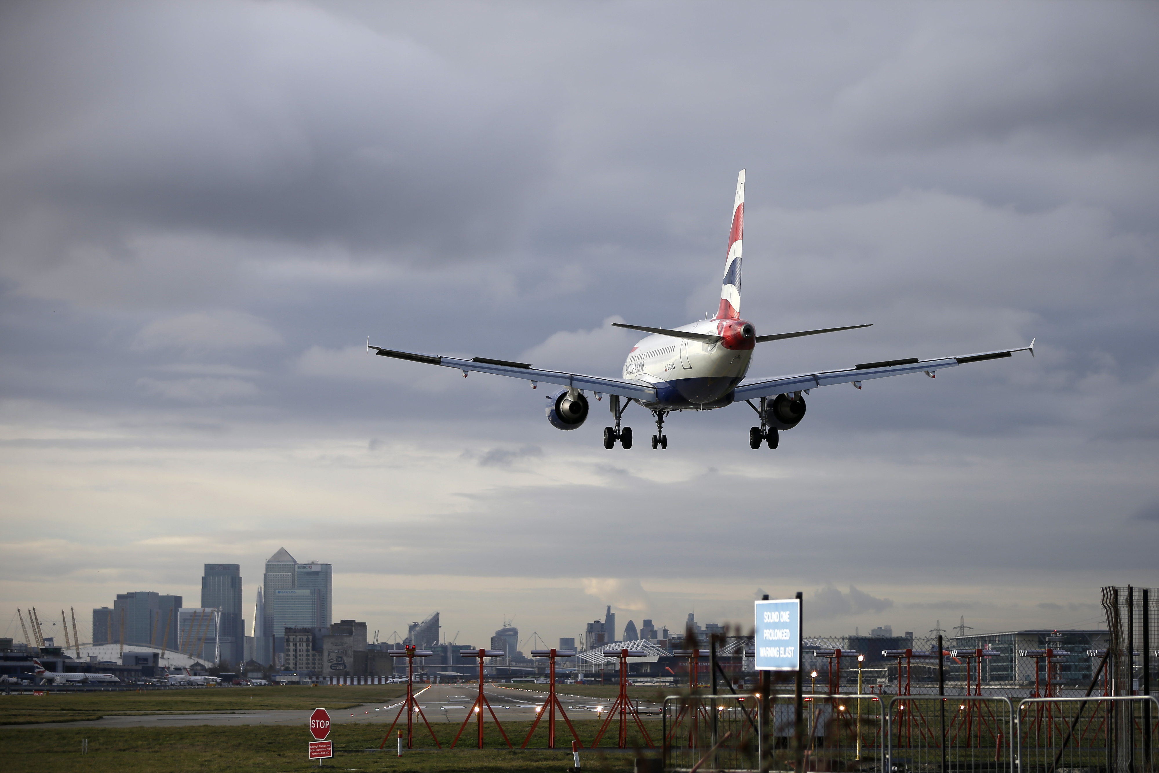 An Embraer SA passenger aircraft, operated by British Airways, a unit of International Consolidated Airlines Group SA (IAG), comes in to land on a runway at London City Airport as commercial skyscrapers of the Canary Wharf business and shopping district stand beyond in London, U.K., on Tuesday, Jan. 21, 2014.