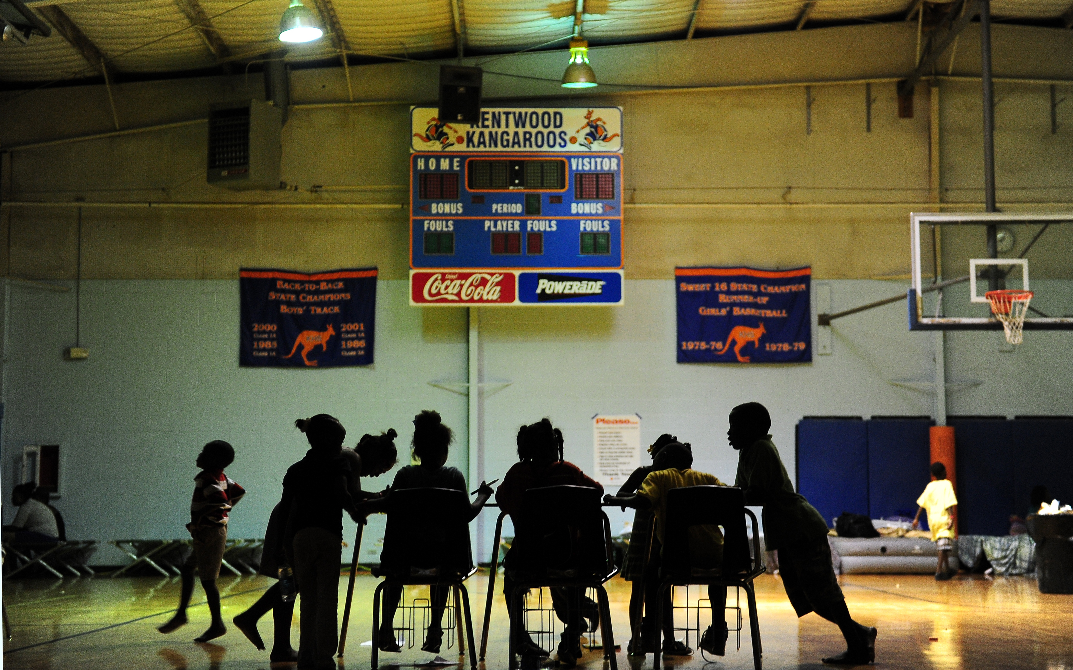 Children try to do their homework at an evacuation shelter in a high school gymnasium in Kentwood, Louisiana on August 30, 2012.