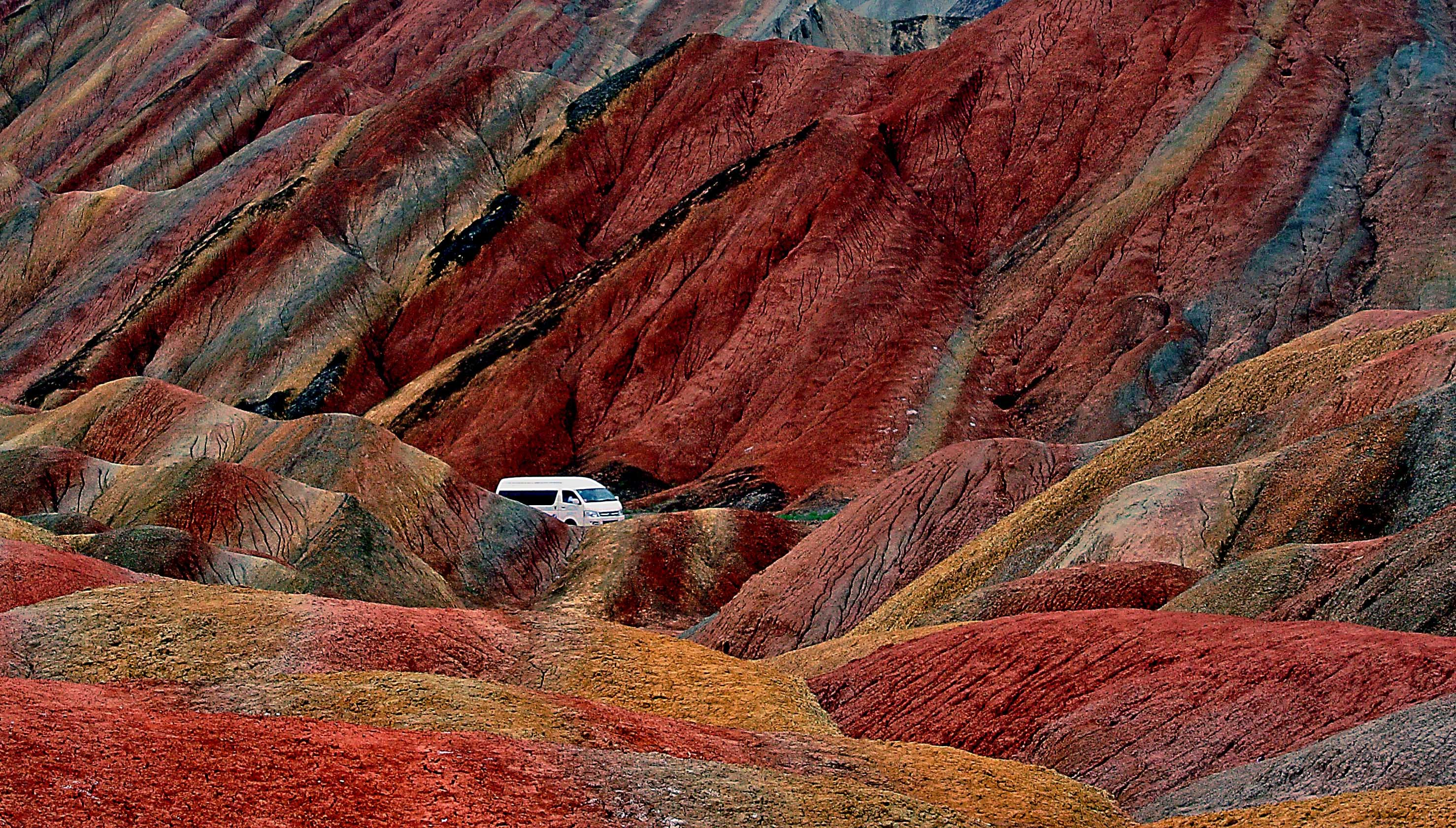A minibus passes by the Danxia landform scenic area. Danxia, which means  rosy cloud , is a special landform formed from reddish sandstone that has been eroded over time into a series of mountains surrounded by curvaceous cliffs and many unusual rock formations, Zhangye City, Gansu Province, northwest China, July 7, 2014.