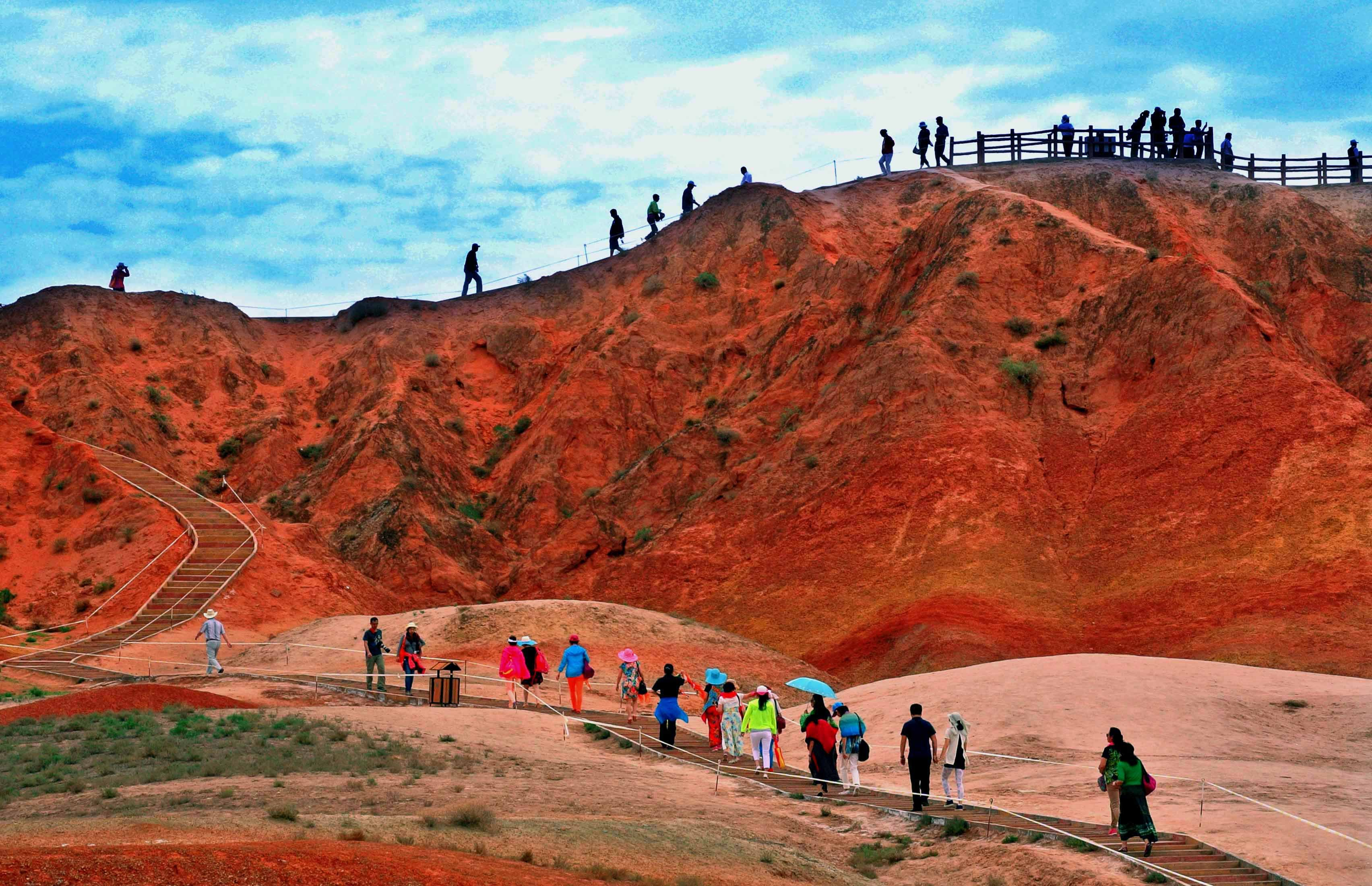 Visitors take in the  scenery at Zhangye Danxia Landform Geological Park in Zhangye City, Gansu Province, northwest China, July 7, 2014.