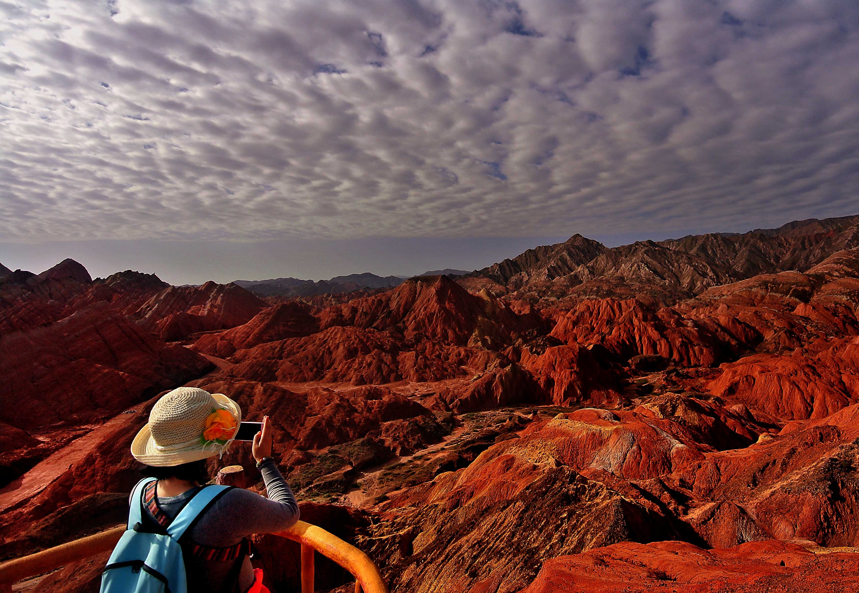 A visitor takes photos at Zhangye Danxia Landform Geological Park in Zhangye City, Gansu Province, northwest China, July 7, 2014.