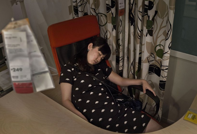 A shopper sleeps in an offfice chair in the showroom of the IKEA store on July 6, 2014 in Beijing.