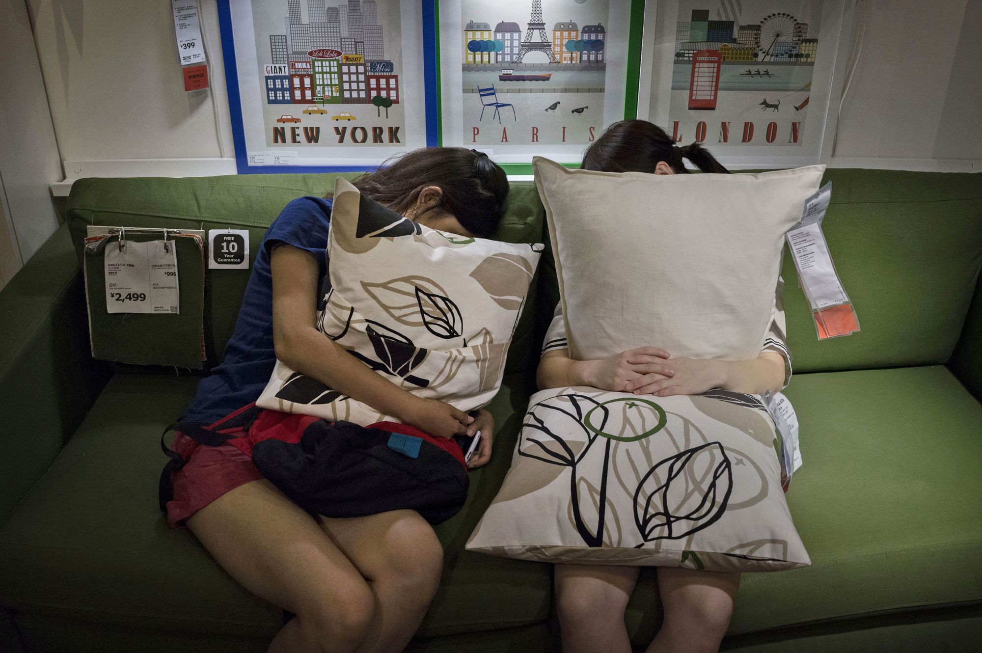 Shoppers clutch pillows as they sleep on a sofa in the showroom of the IKEA store on July 6, 2014 in Beijing.