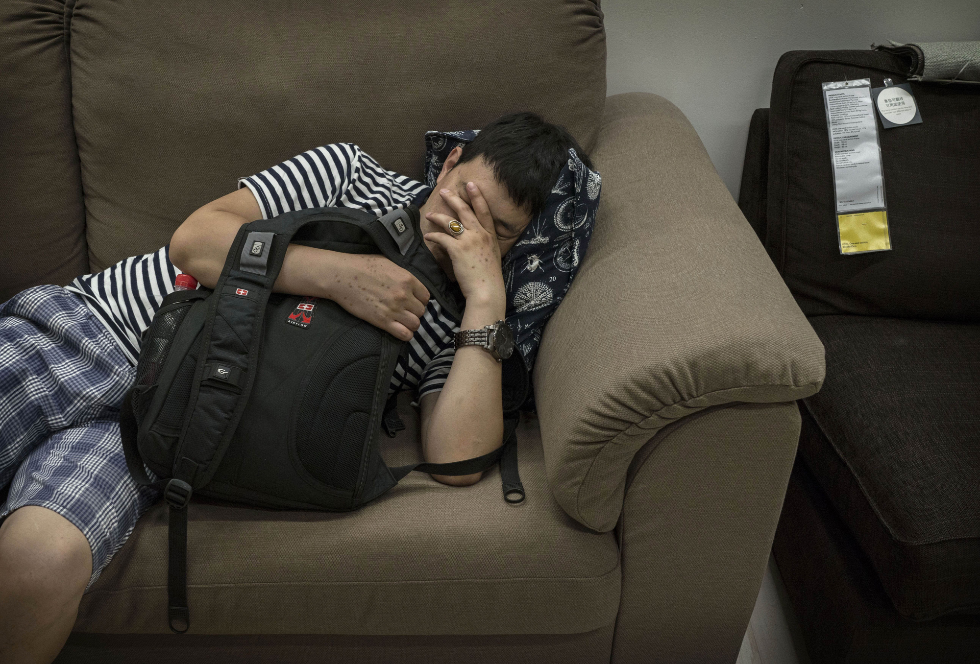 A shopper sleeps on a sofa in the showroom of the IKEA store on July 6, 2014 in Beijing.