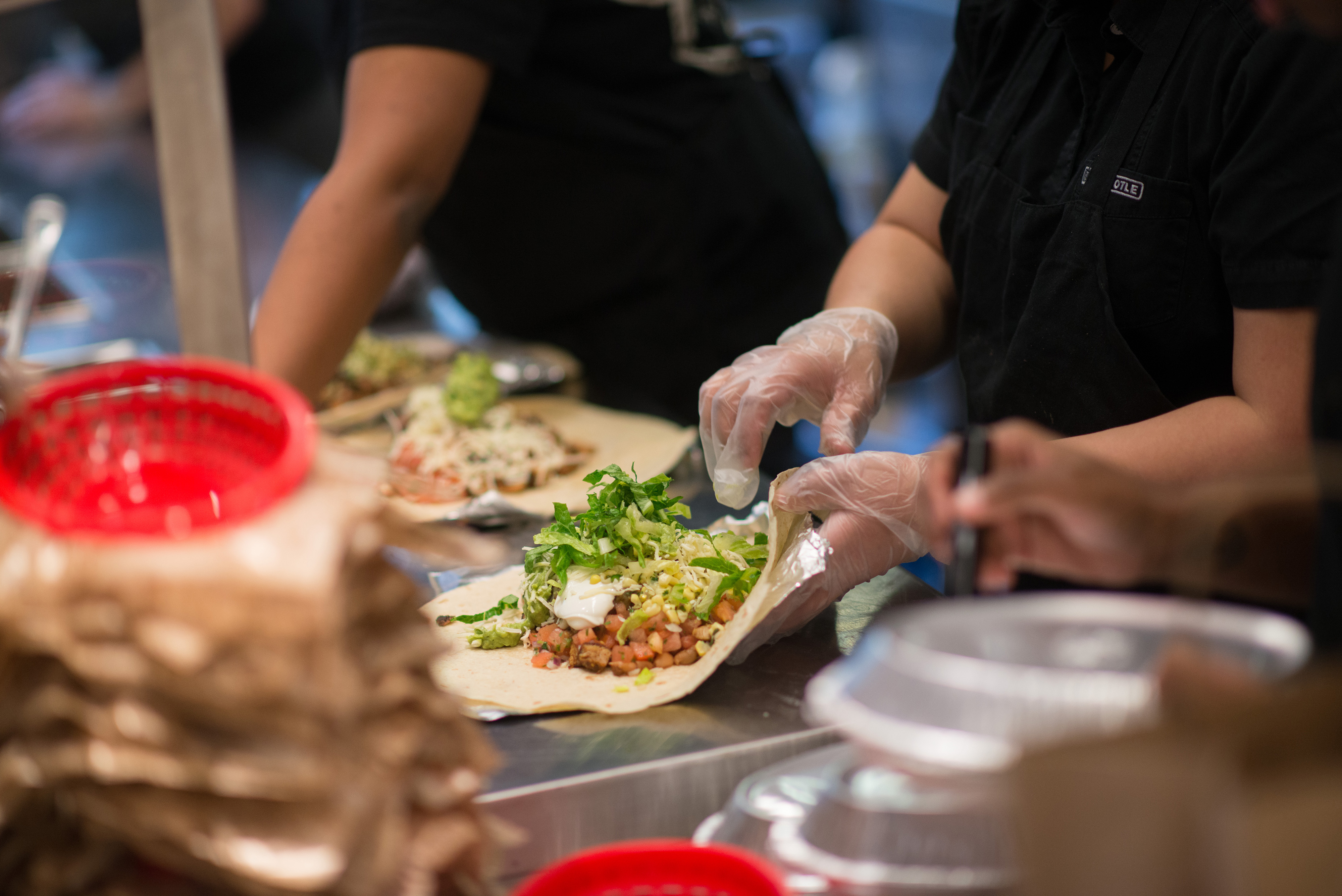 Employees prepare lunch orders at a Chipotle Mexican Grill restaurant at Madison Square Park in New York, U.S., on Wednesday, Jan. 29, 2014.