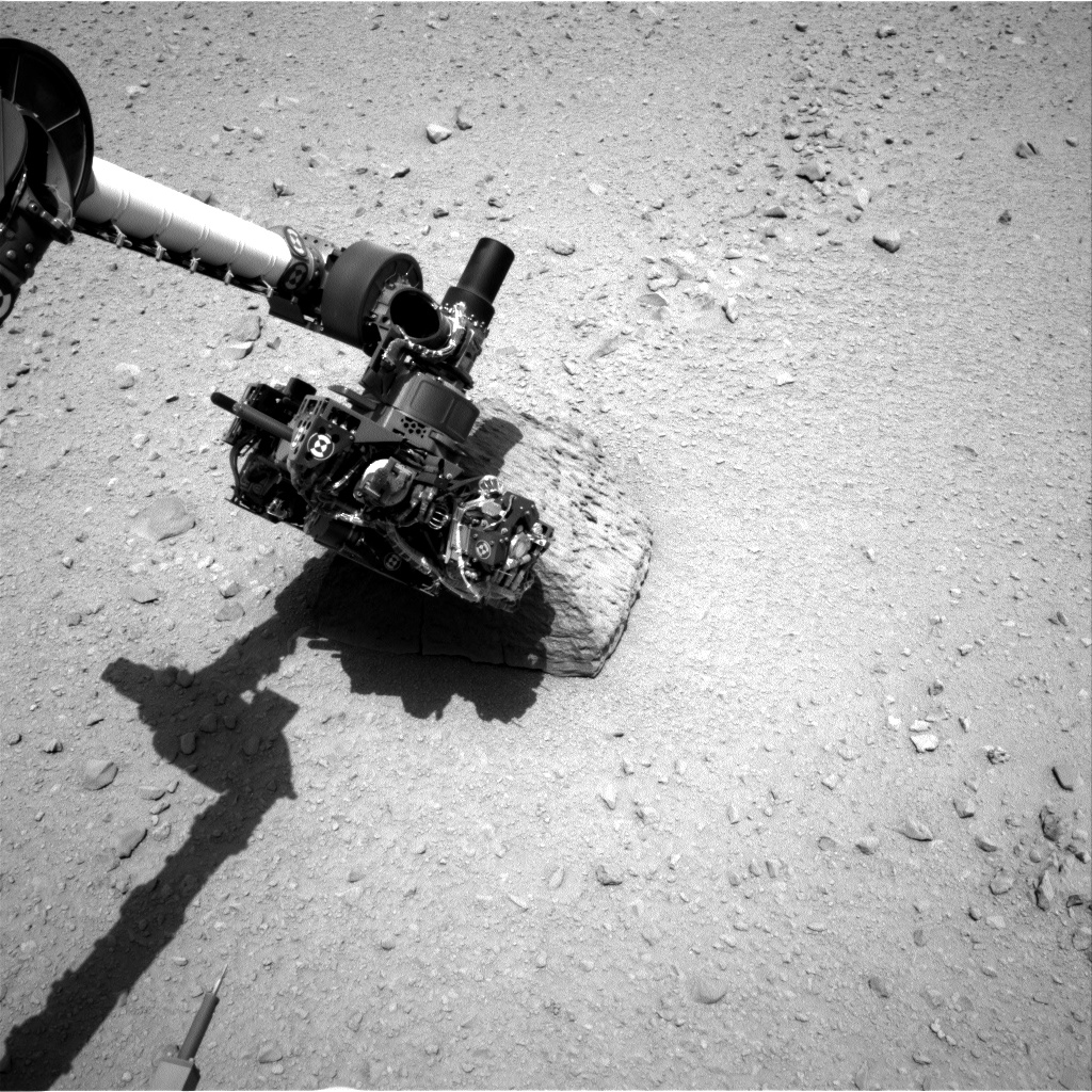 This image shows the robotic arm of NASA's Mars rover Curiosity with the first rock touched by an instrument on the arm. The rover's right Navigation Camera (Navcam) took this image during the 46th Martian day, or sol, of the mission (Sept. 22, 2012).