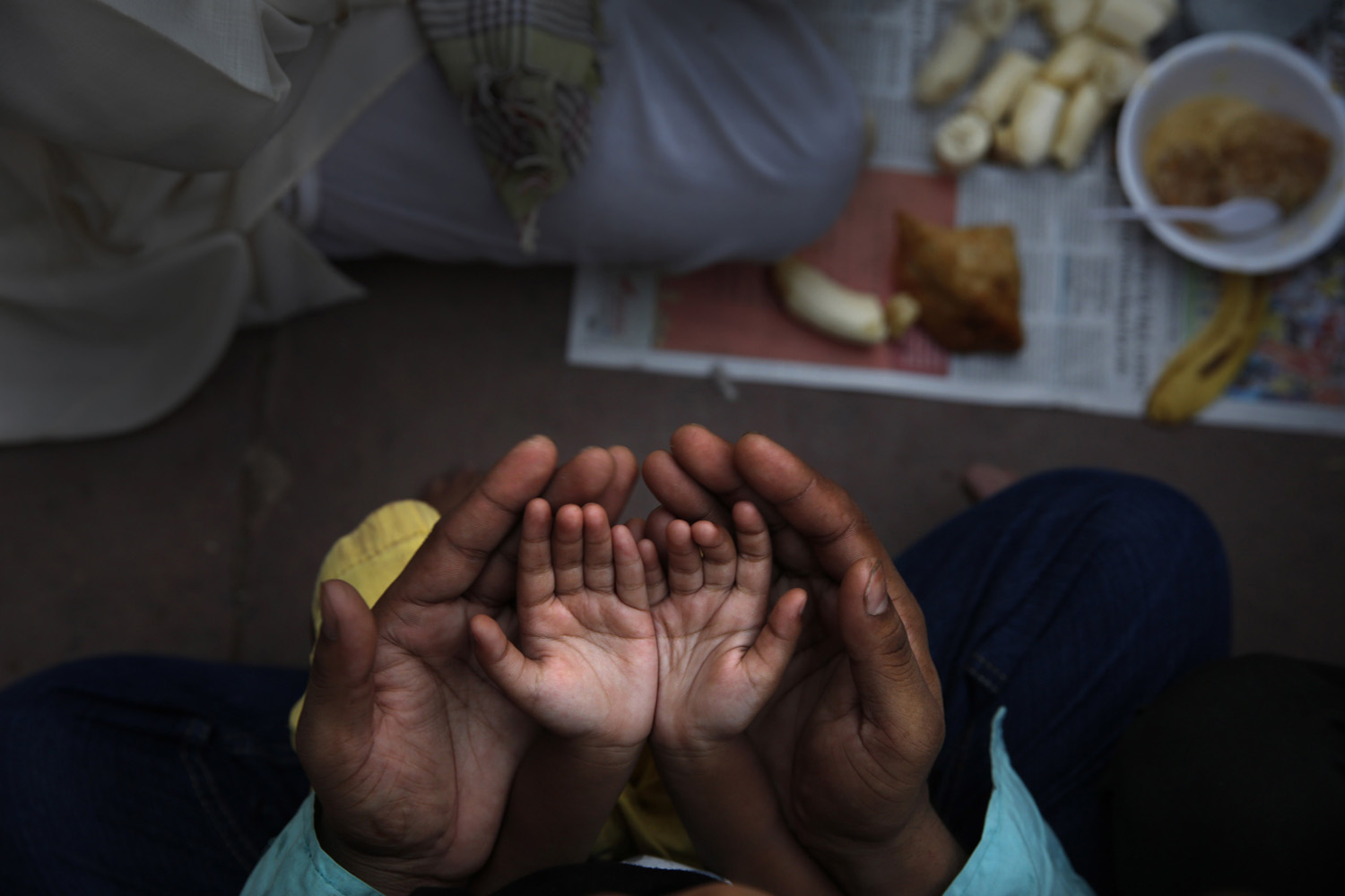Jun. 30, 2014. An Indian Muslim father holds the hands of his daughter in his palms and prays before  breaking fast on the first day of holy month Ramadan at the Jama Mosque in New Delhi, India.