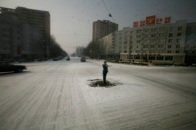 A traffic guard stands in the center of a snowy street in Pyongyang, North Korea on Feb. 26, 2008.