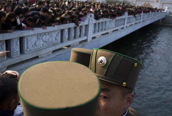 North Korean soldiers and civilians stand on a foot bridge to look at goldfish in a moat as they tour the grounds of Kumsusan Palace of the Sun, the mausoleum where the bodies of the late leaders Kim Il Sung and Kim Jong Il lie embalmed, in Pyongyang on April 25, 2013.