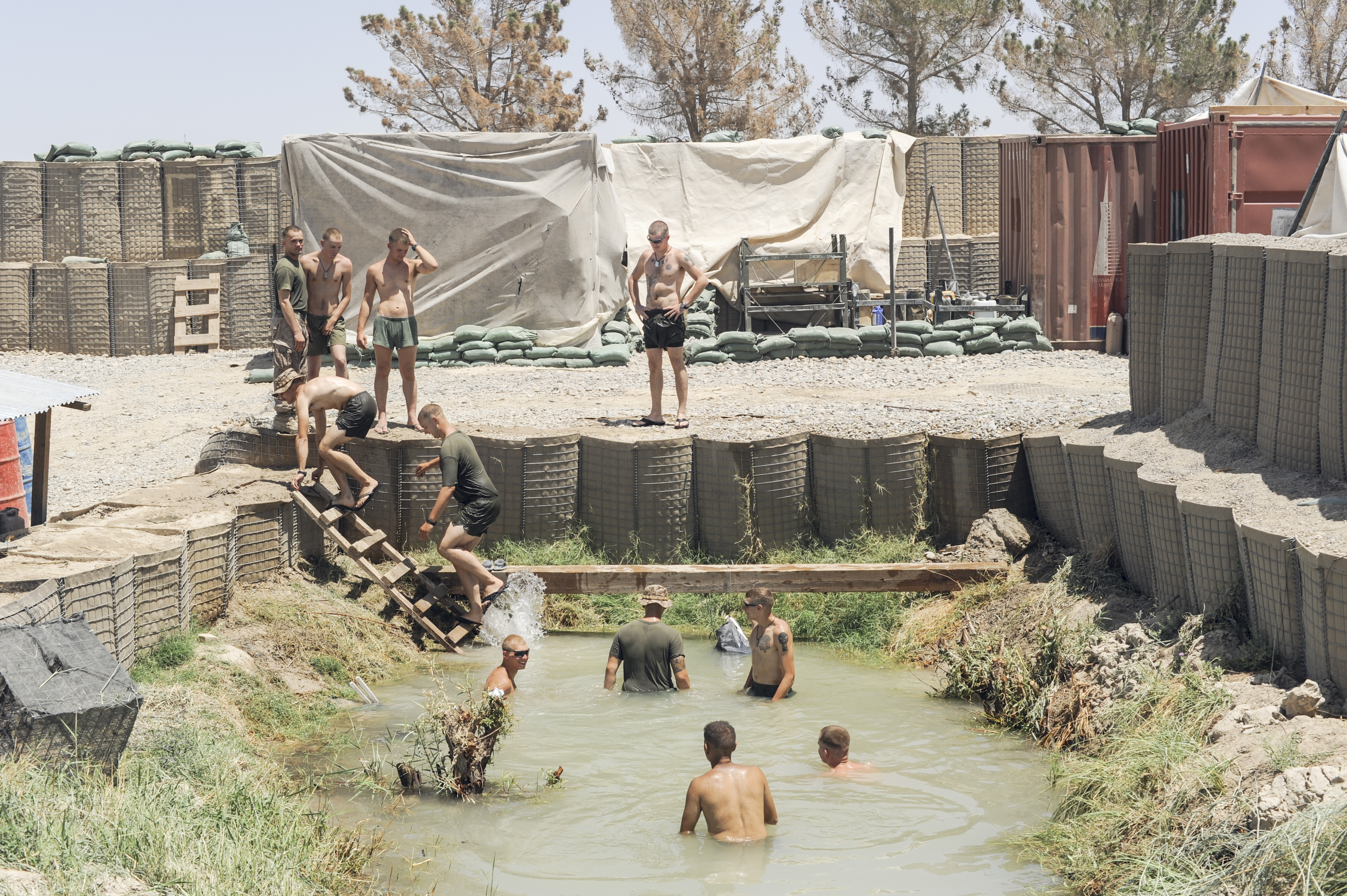Marines swim in an irrigation canal at their outpost in Helmand Province.                               South of Garmsir, Helmand. Afghanistan. 2009