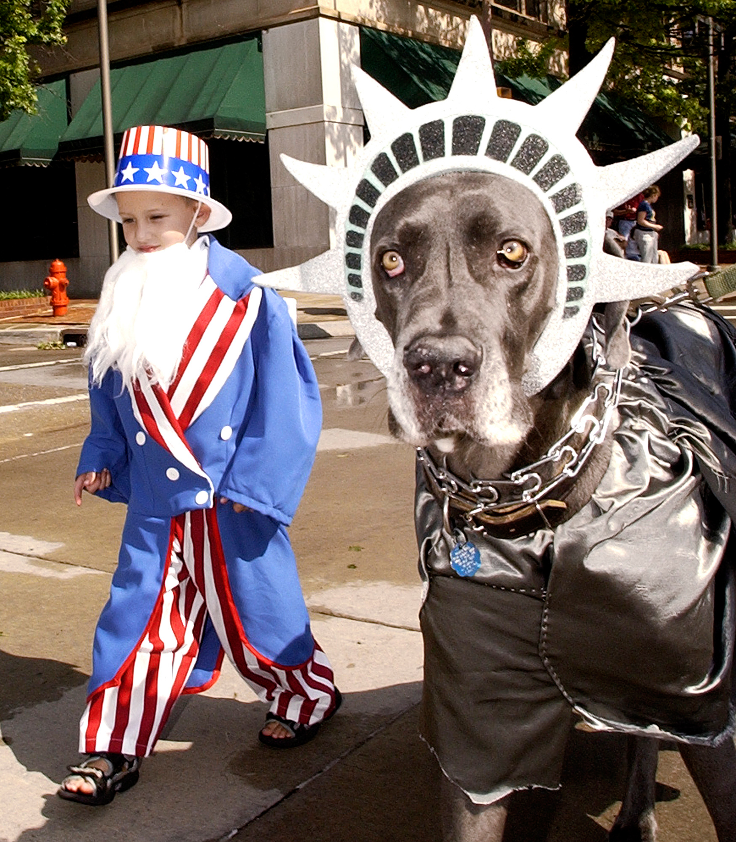 Zachary Harris, 5, of Moore, Okla., dressed as Uncle Sam, walks with his dog, Brutus, dressed as  Lady Liberty  in the Downtown Salute Parade, July 4, 2005, in Oklahoma City, as part of the parade's Most Patriotic Dog Competition.