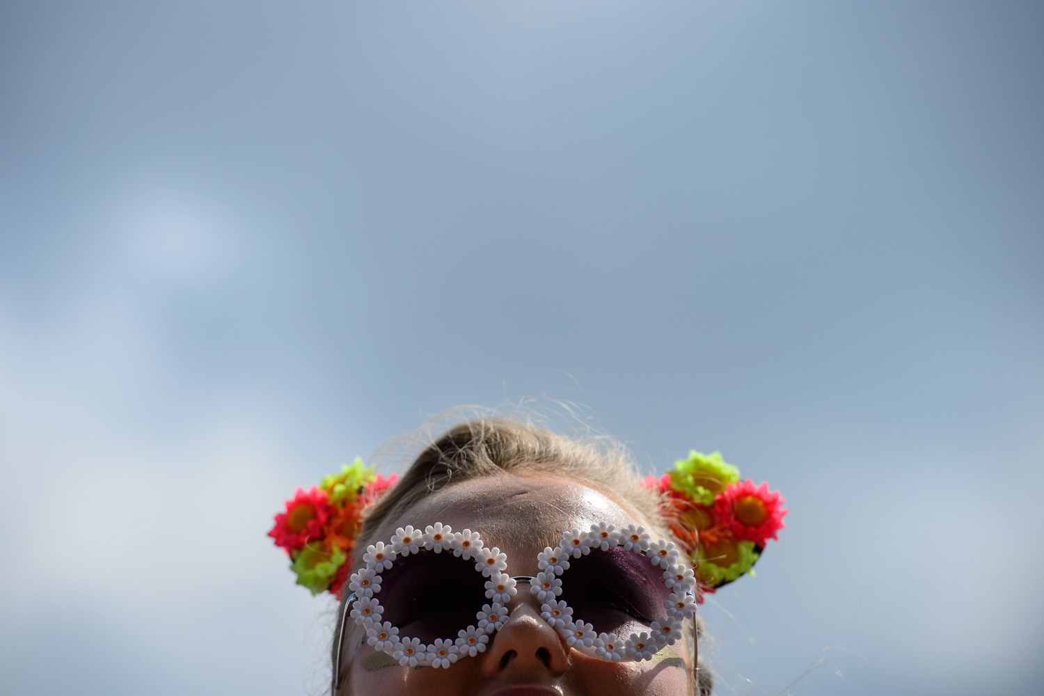 A girl waits for the first act to take to the Pyramid Stage on the last day of the Glastonbury Festival of Music and Performing Arts in Somerset, southwest England, on June 29, 2014.