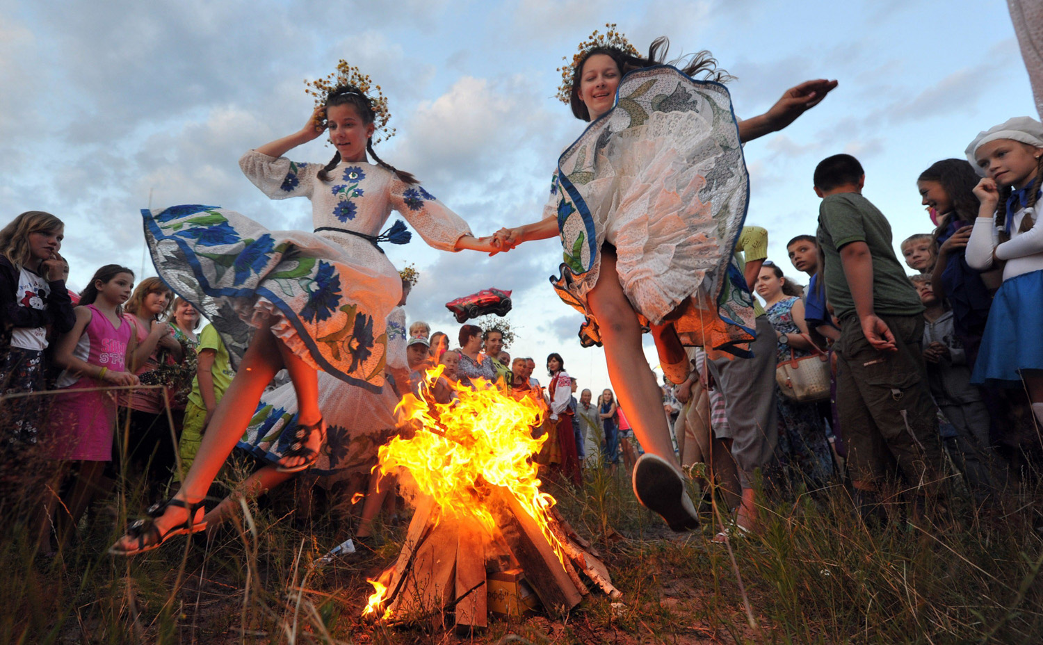 Wearing traditional Belarus costumes, girls jump over a bonfire as they celebrate the Ivan Kupala night, an ancient heathen holiday, held in the countryside near the town of Turov, some 260 km southwest of the capital Minsk, Belarus on July 6, 2014.