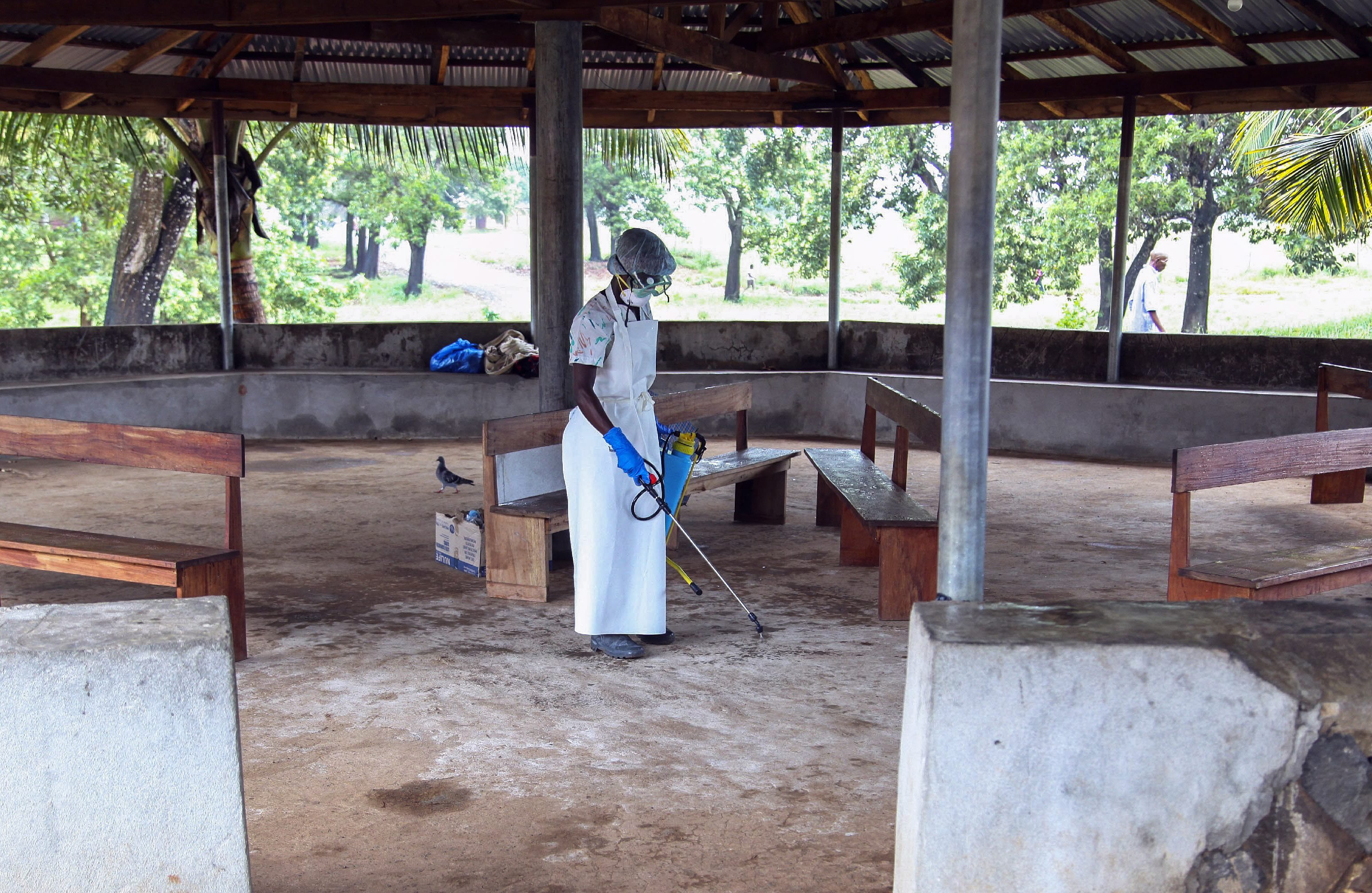 A nurse from Liberia sprays preventives to disinfect the waiting area for visitors at the ELWA Hospital where a US doctor Kent Bradley is being quarantined in the hospitals isolation unit having contracted the Ebola virus, Monrovia, Liberia, 28 July 2014.