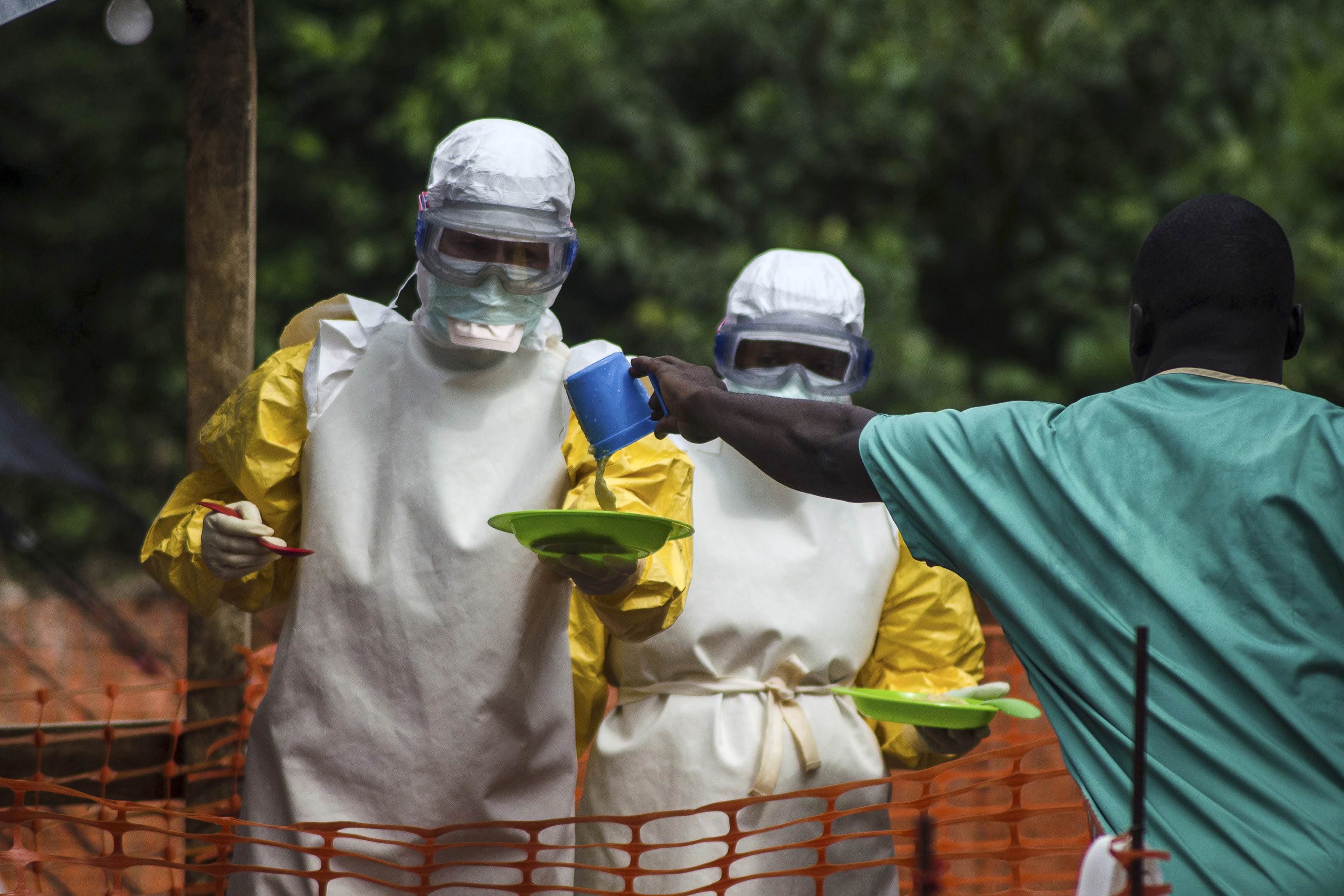 Medical staff working with Medecins sans Frontieres (MSF) prepare to bring food to patients kept in an isolation area at the MSF Ebola treatment centre in Kailahun, Sierra Leone on July 20, 2014.