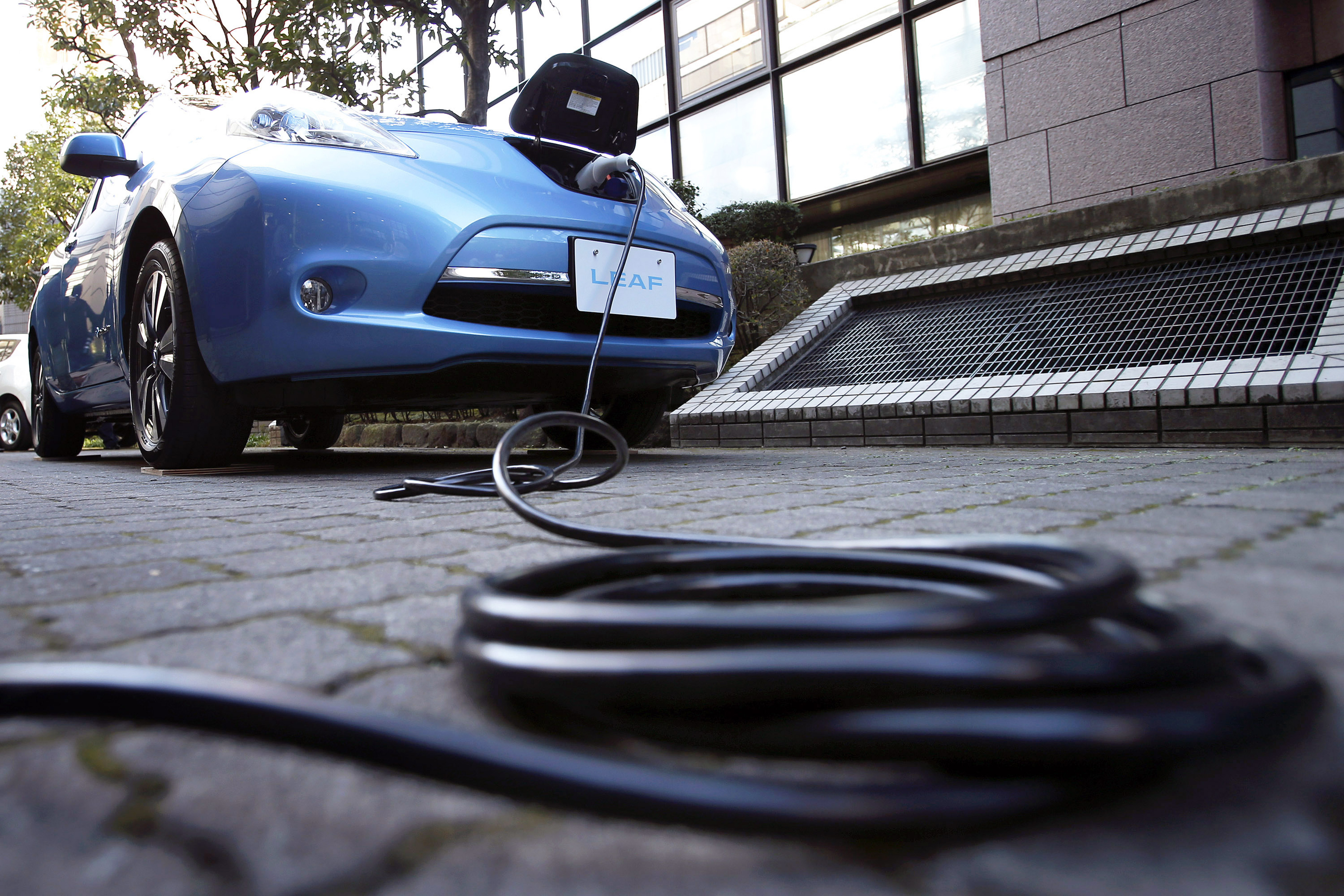 An electric charging cable is seen connected to the updated Nissan Leaf vehicle during a news conference in Japan, Tokyo, on Tuesday, Nov. 20, 2012.