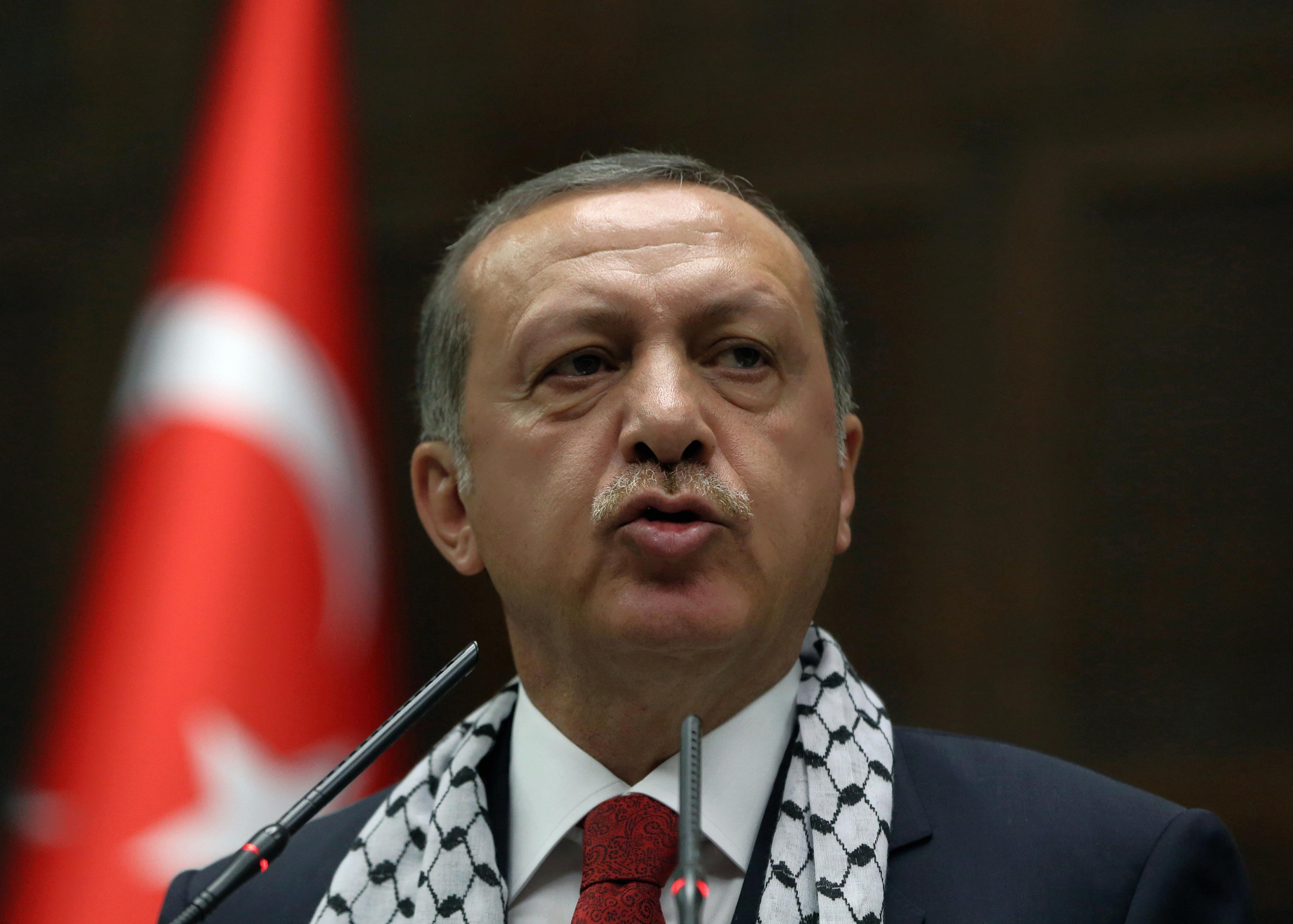 Turkish Prime Minister Recep Tayyip Erdogan addresses his supporters at parliament wearing a Palestinian keffiyeh, in Ankara, July 22, 2014.