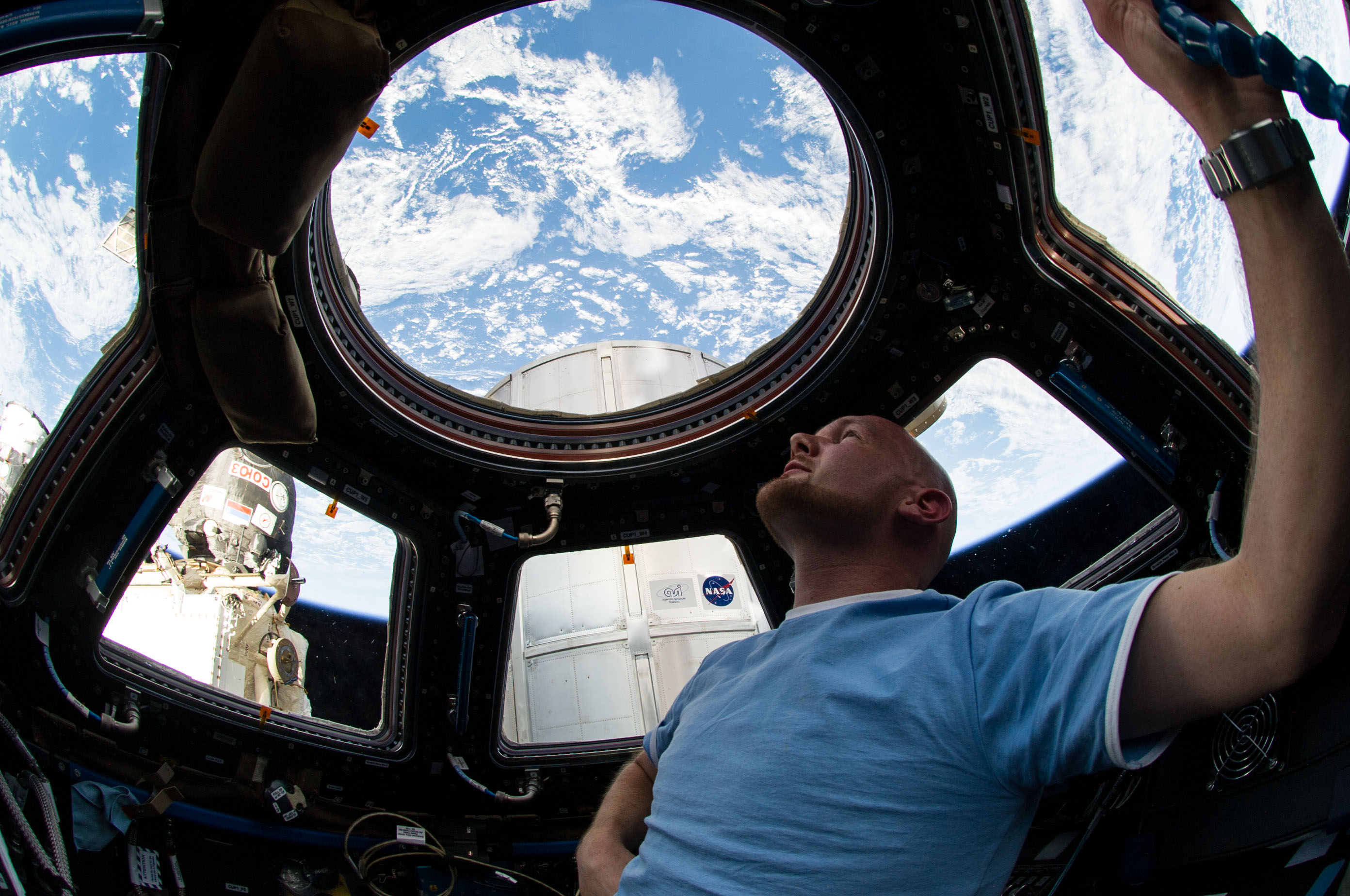 Astronaut Alexander Gerst enjoys the view of Earth from the windows in the Cupola of the International Space Station. A blue and white part of Earth is visible through the windows.