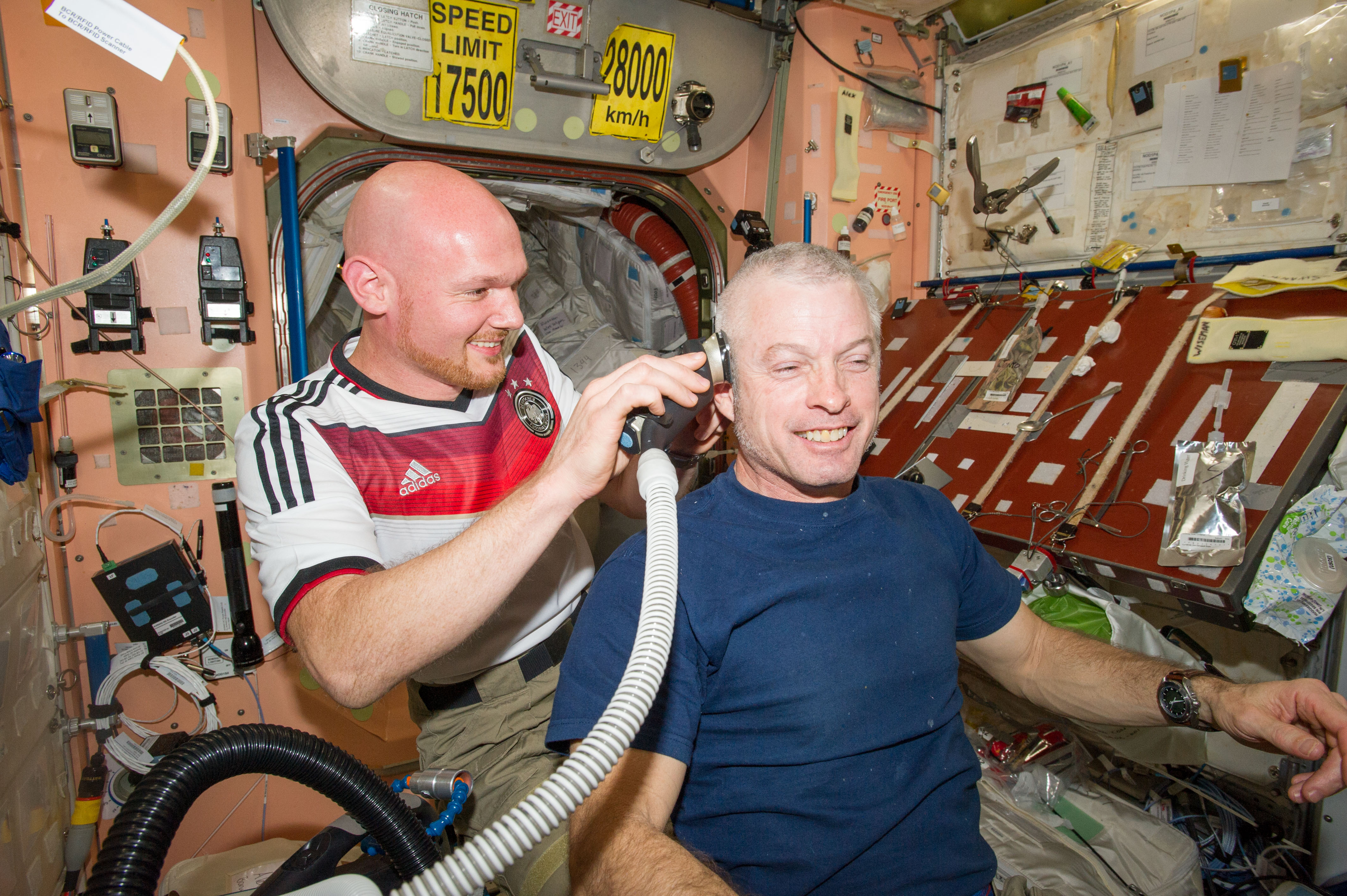 Astronaut Alexander Gerst shaves the head of NASA astronaut Steve Swanson in the Unity node of the International Space Station. Gerst used hair clippers fashioned with a vacuum device.
