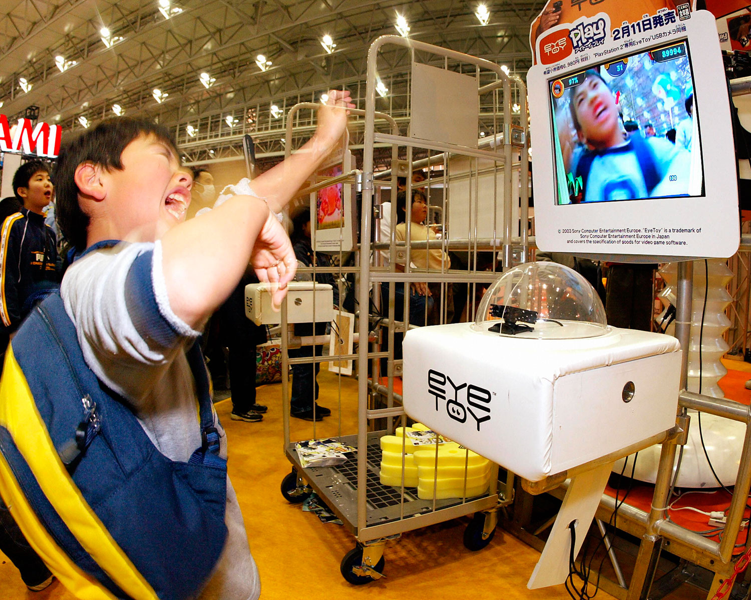 A Japanese boy tries out Sony Computer Entertainment's 'eye TOY' motion capture camera for the company's PlayStation 2 video game console at the World Hobby Fair in Makuhari, Tokyo on January 24, 2004.